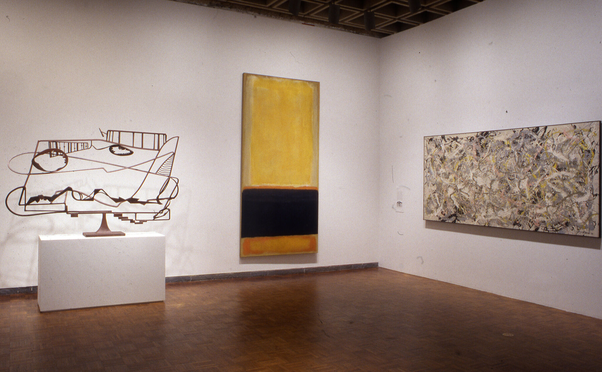 Two paintings and a wire sculpture displayed in a gallery.