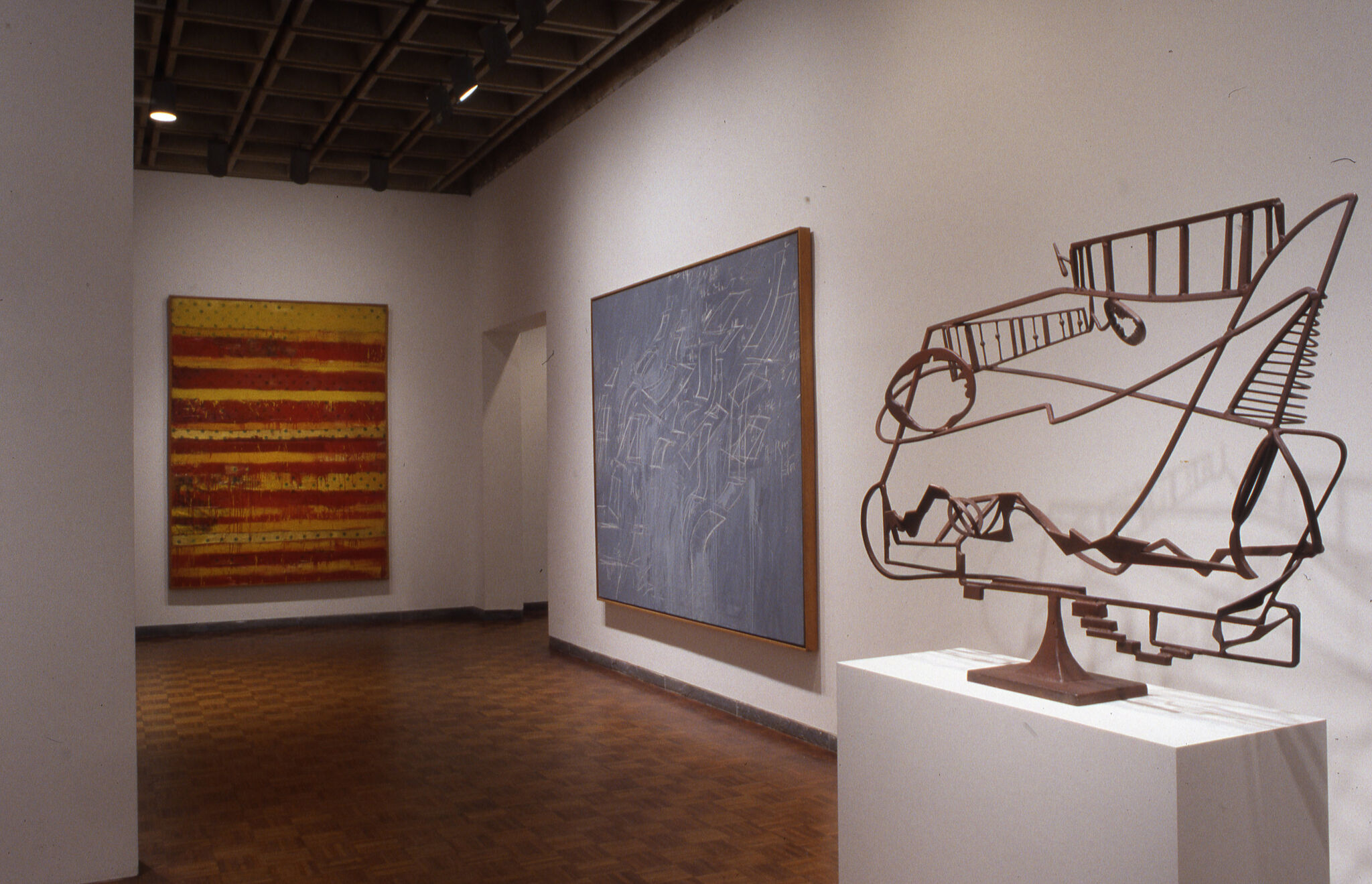 A wire sculpture and two paintings displayed in a gallery.