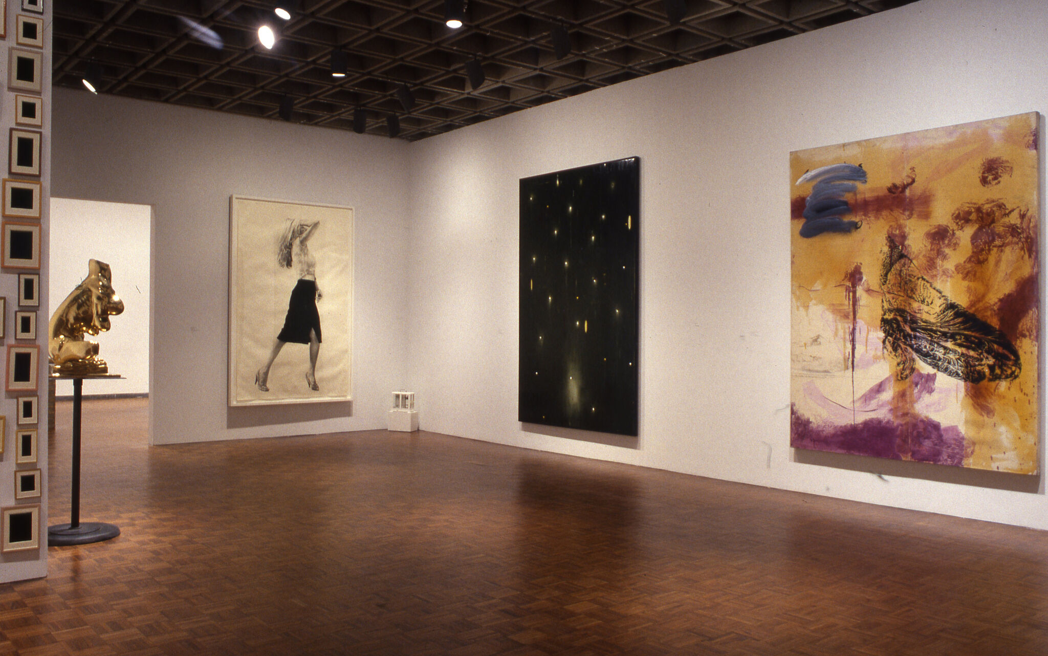A gold sculpture and three paintings displayed in a gallery.