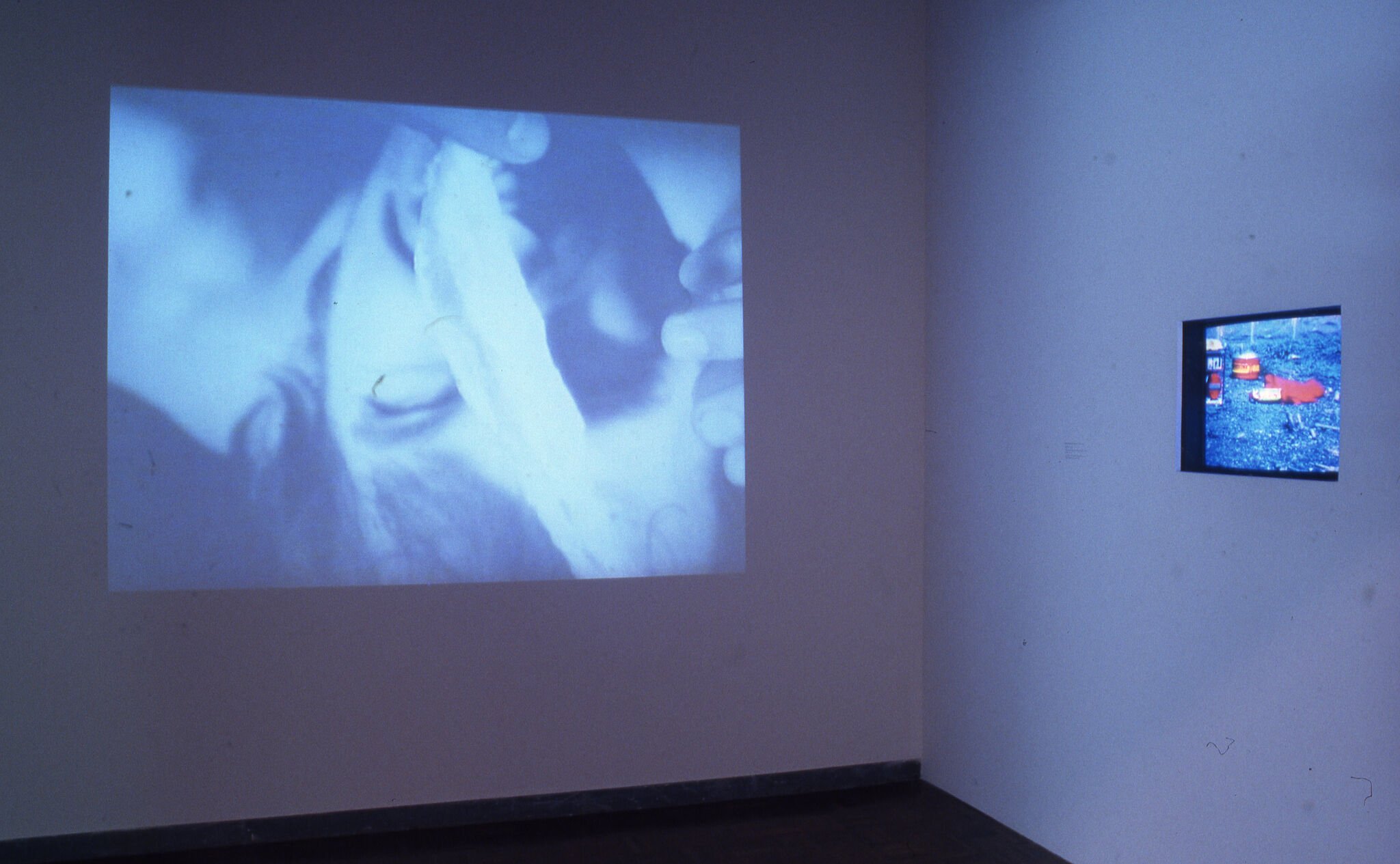 A blue-hued projection of a face, and a monitor embedded on a wall in a gallery.
