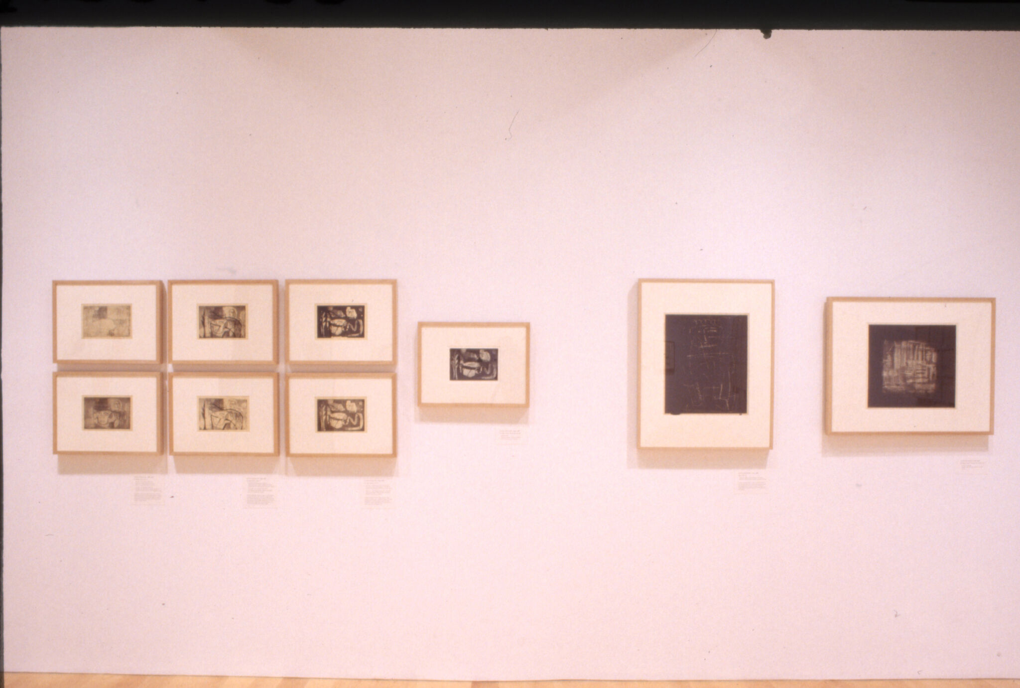 Prints displayed in frames on a wall in a gallery.
