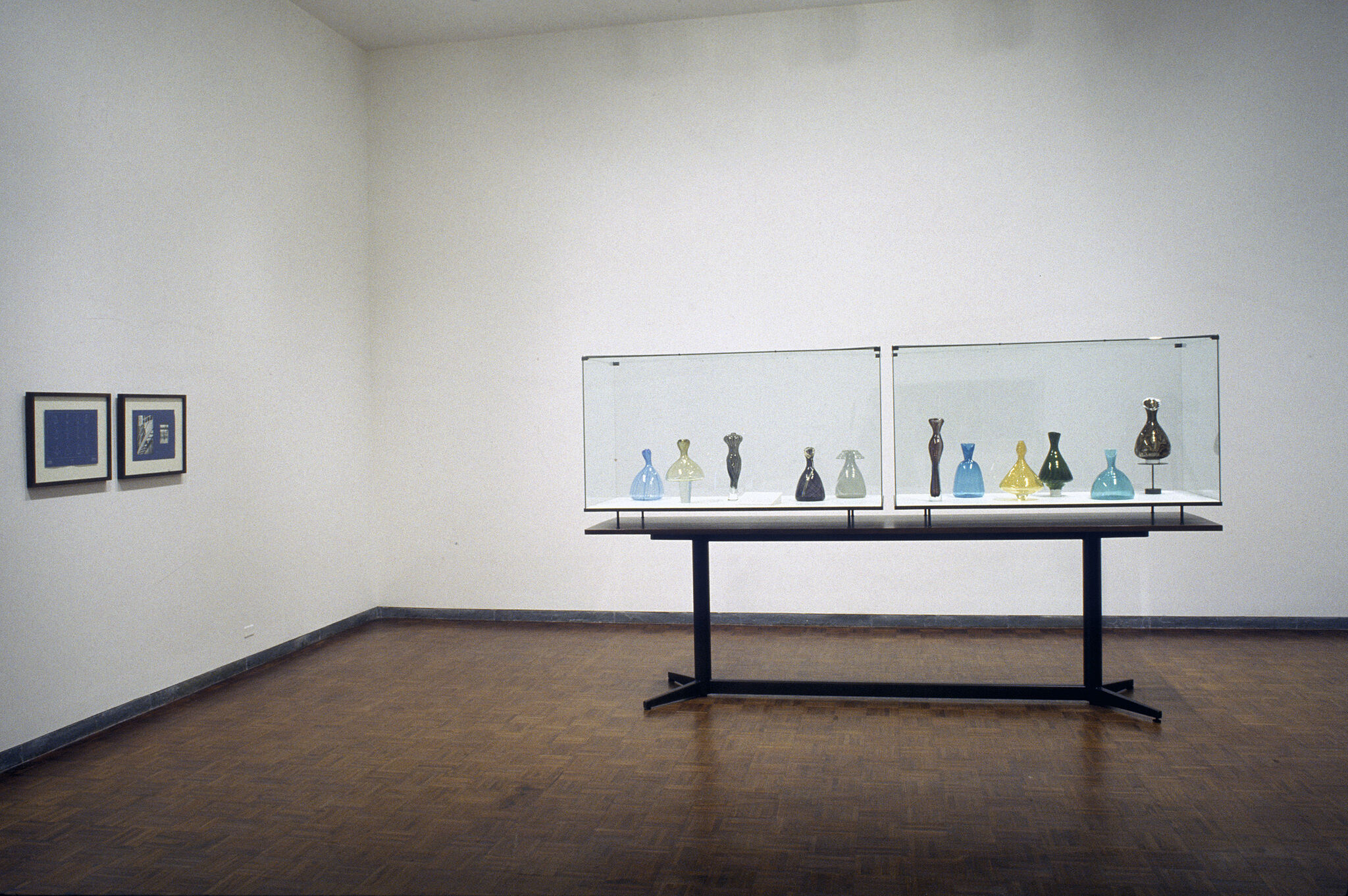 A glass case filled with vases displayed in a gallery.