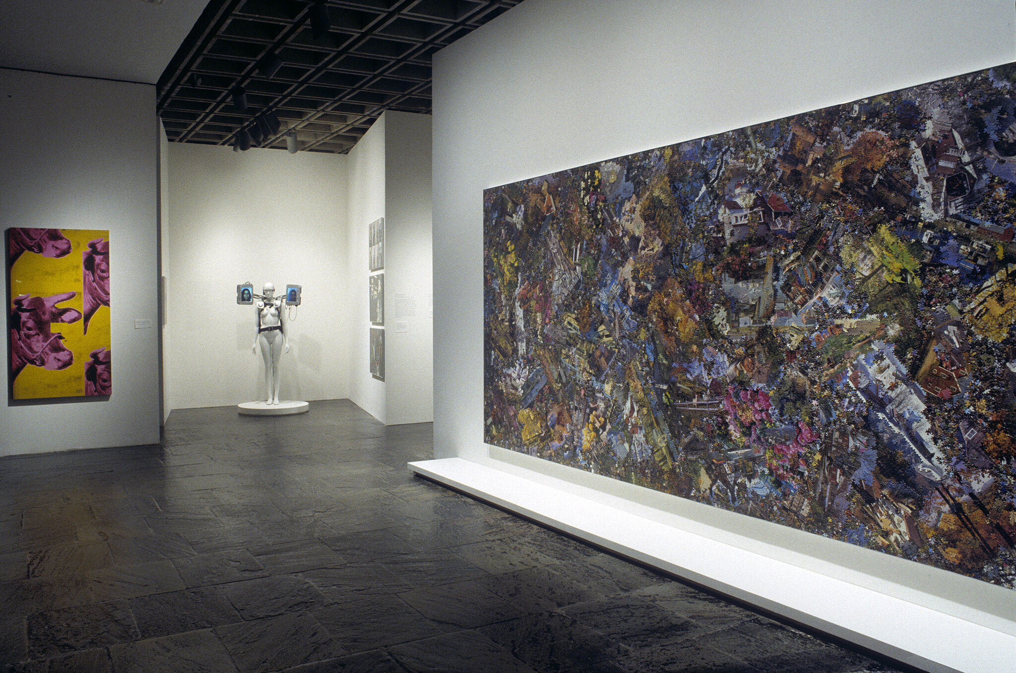 A gallery filled with works of art including paintings and a sculpture.