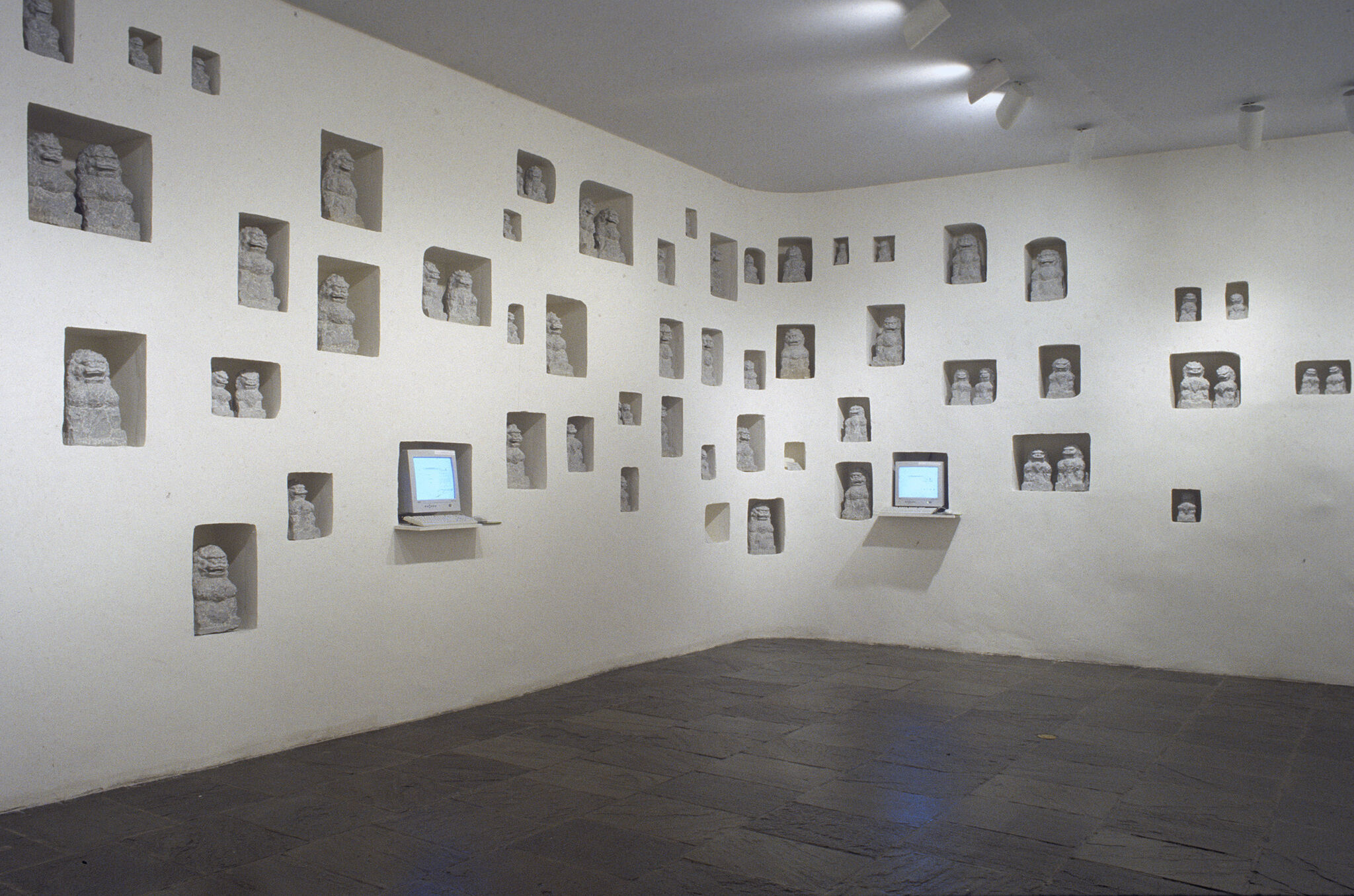 A gallery with sculptures and two small monitors displayed inside the walls.