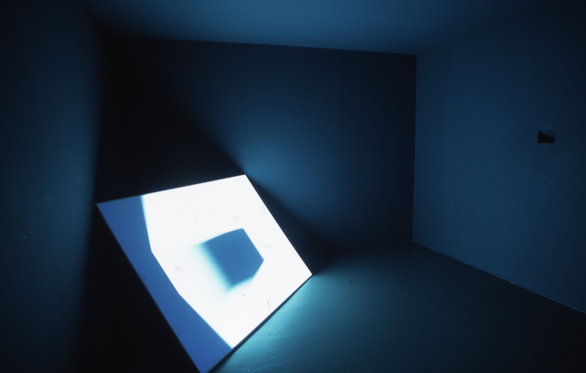A large blue-hued screen displayed in a corner of a gallery.