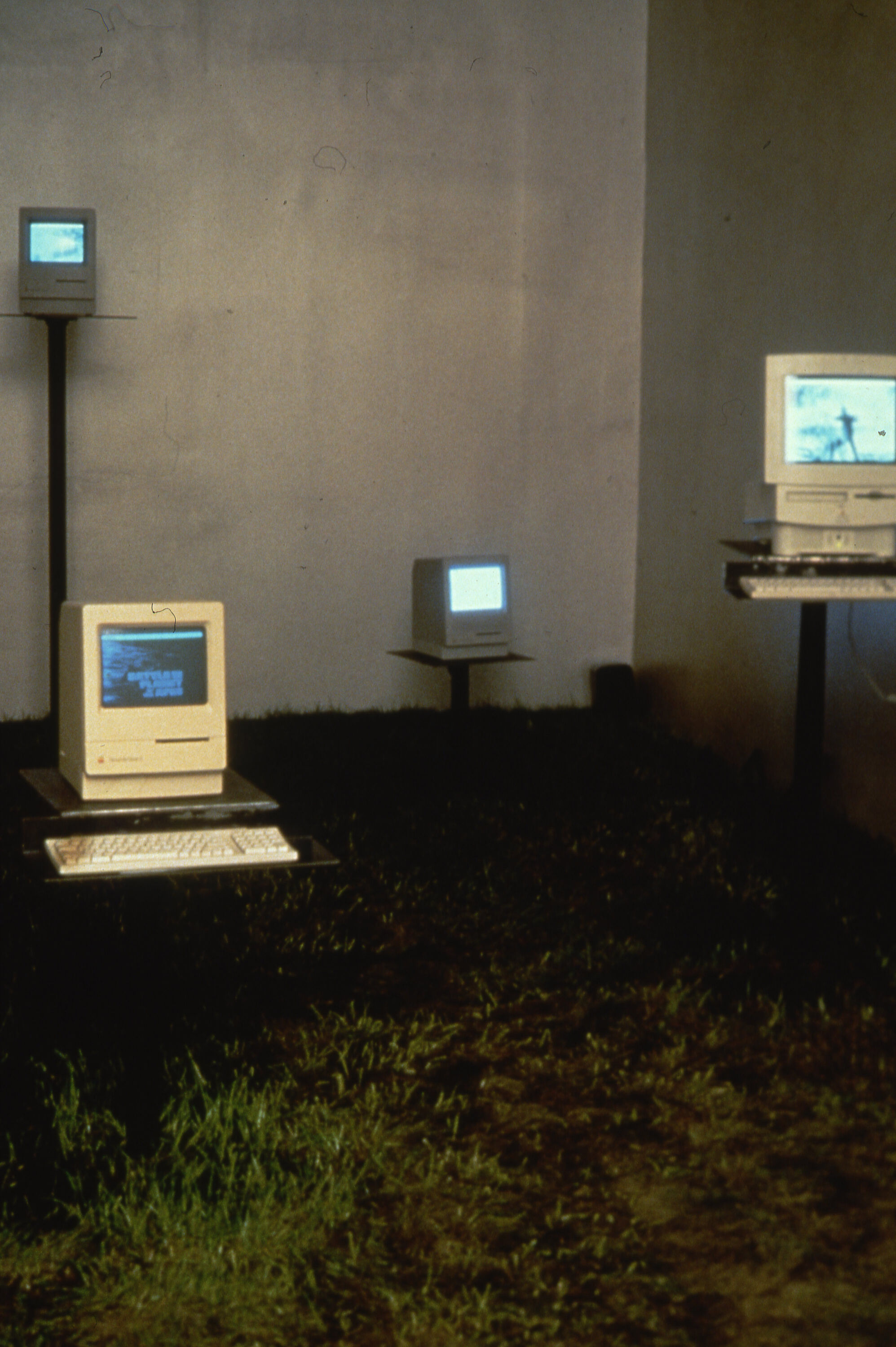 A gallery with grass on the ground and computers displayed on pedestals.