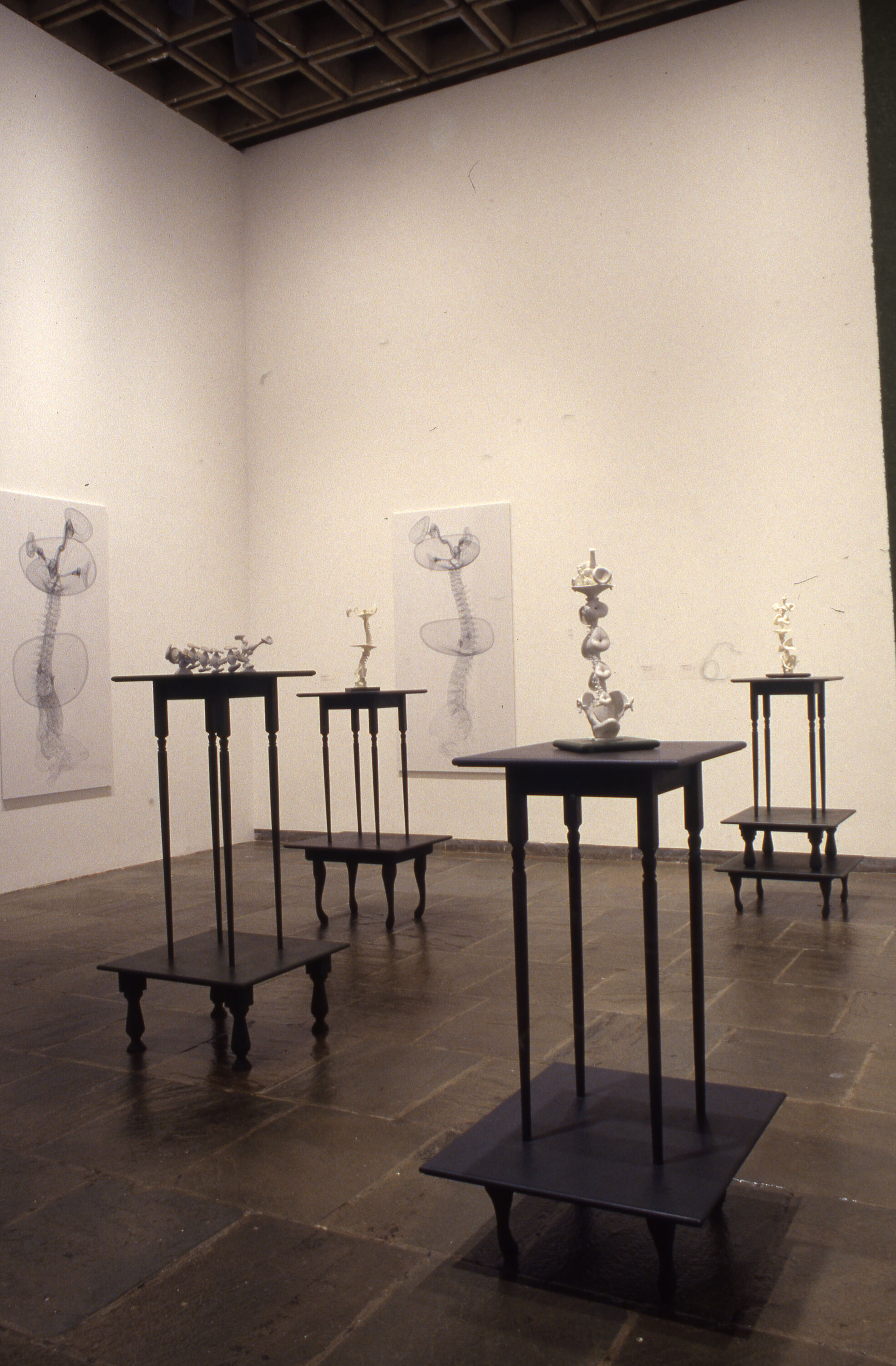 A gallery with white sculptures displayed on top of tall black pedestals.