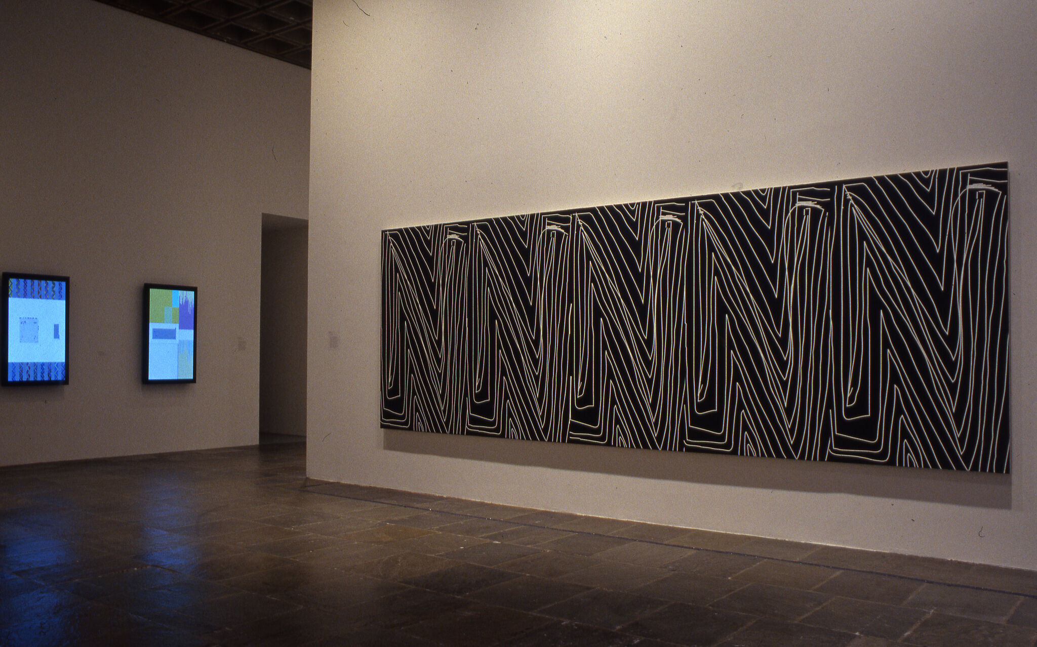A long and rectangular black and white work of art displayed in a gallery.