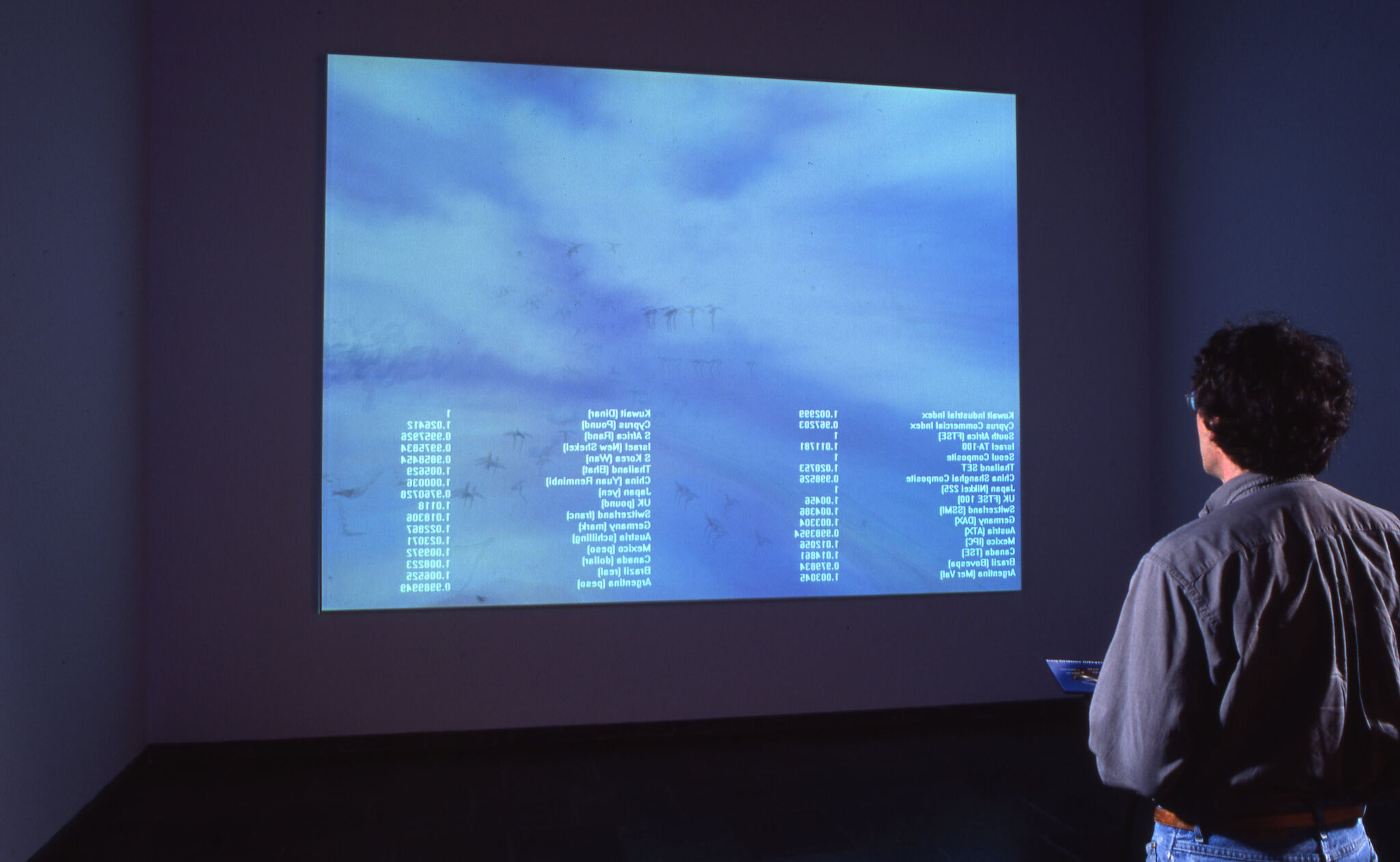 A person looking at a video projection on a wall in a gallery.