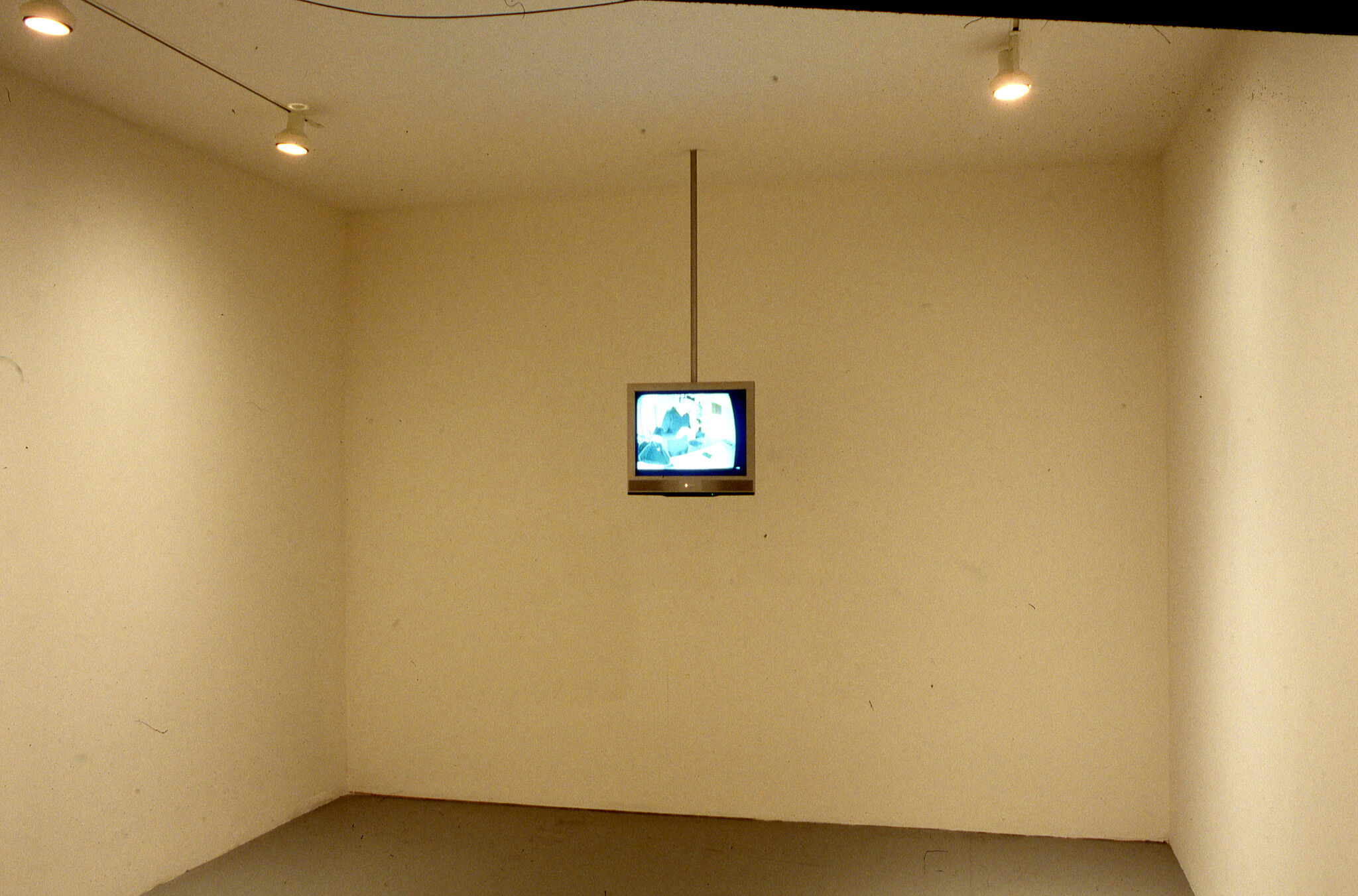 A television set hanging from the ceiling in a gallery.