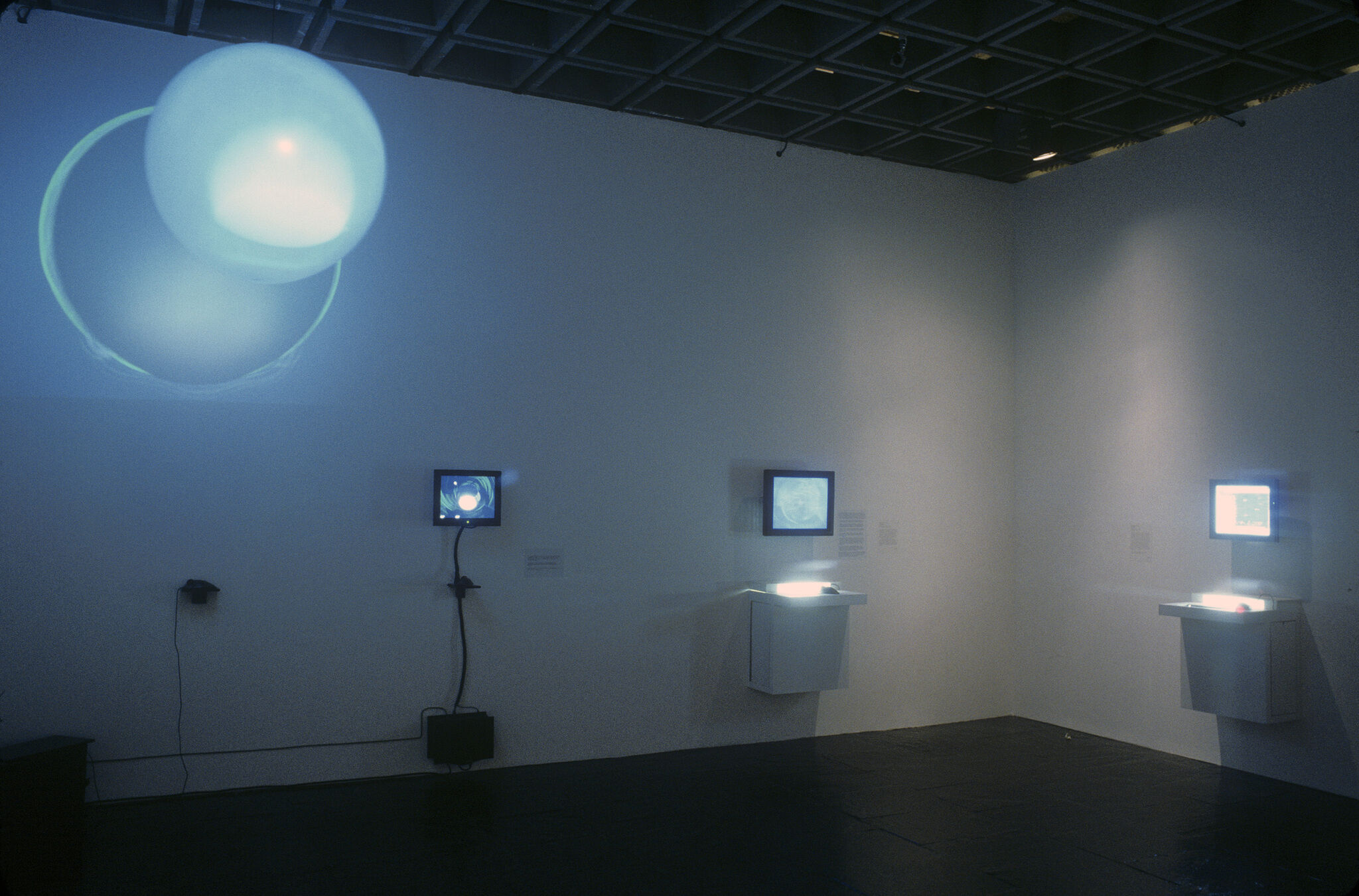 A gallery with a blue-hued video projection, along with monitors mounted on the walls.