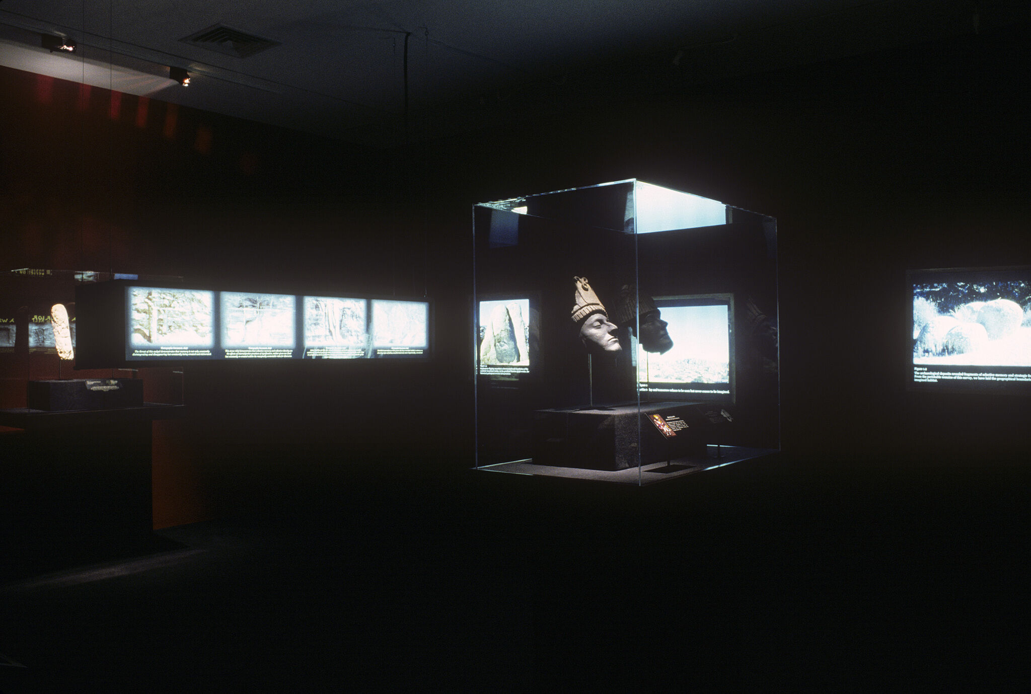 A dark gallery with a sculpture in a glass display case, along with brightly lit monitors around it.