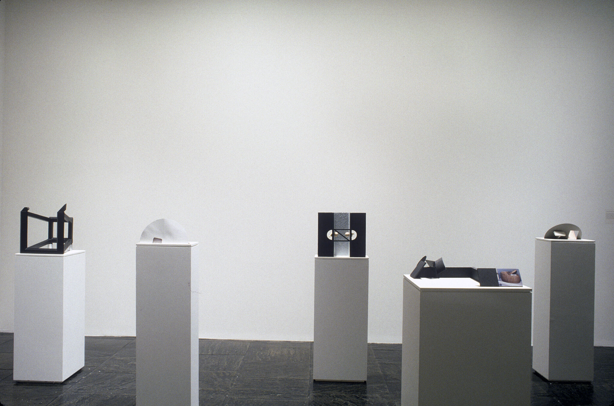 A gallery filled with white podiums displaying various sculptures by Vincent Fecteau.
