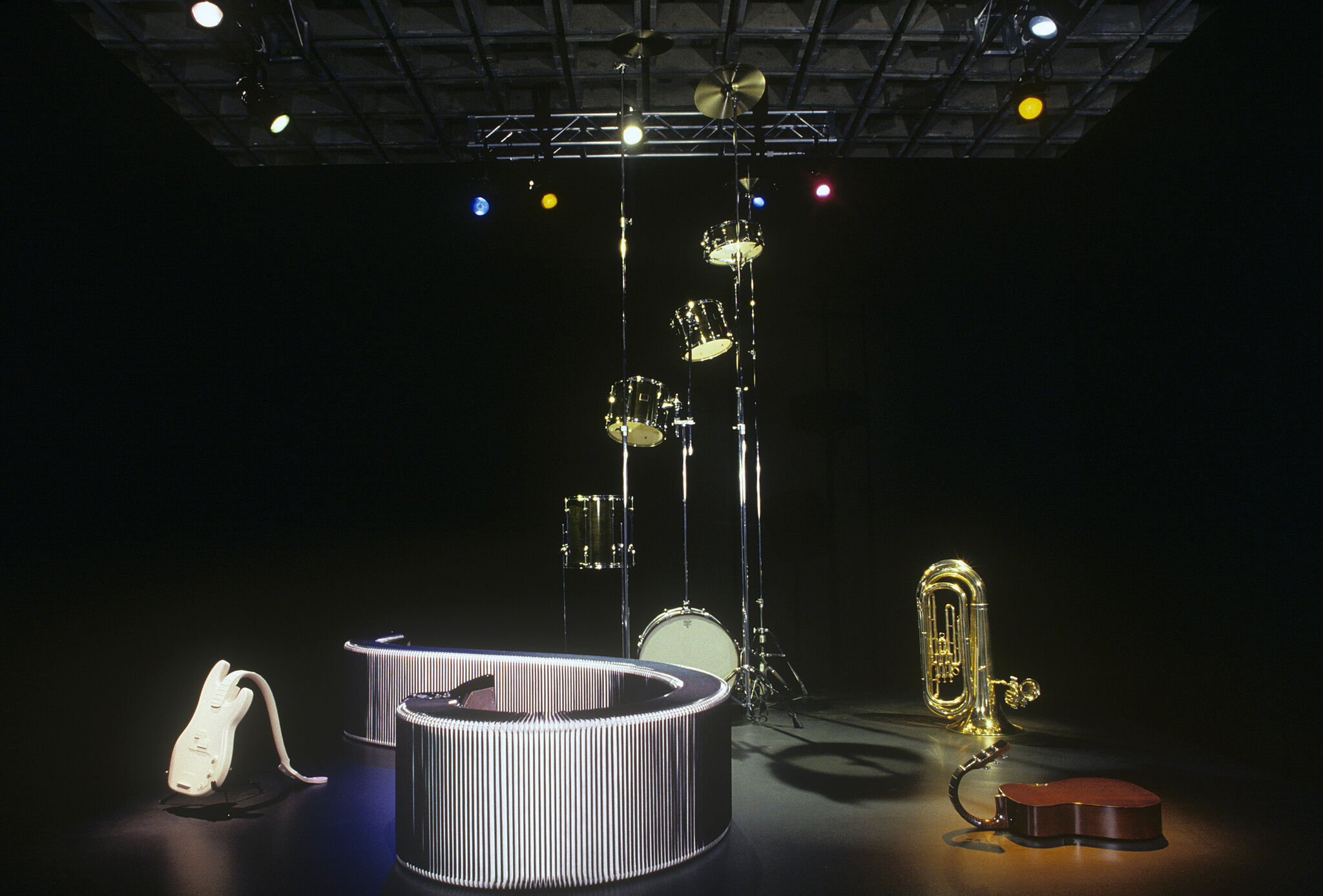 A dark gallery with sculptures of various musical instruments.