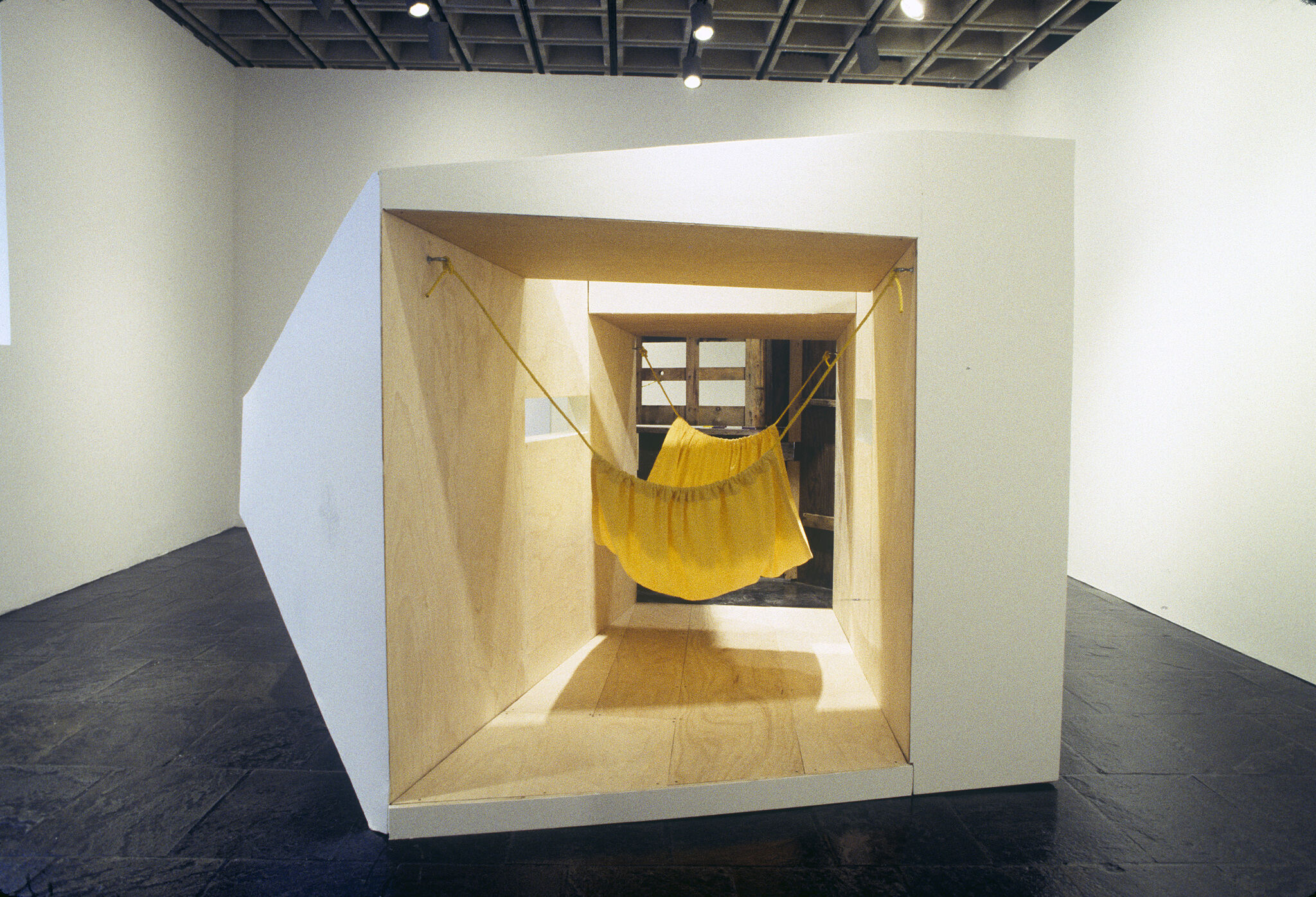 A large white and wooden sculpture with a yellow hammock inside.