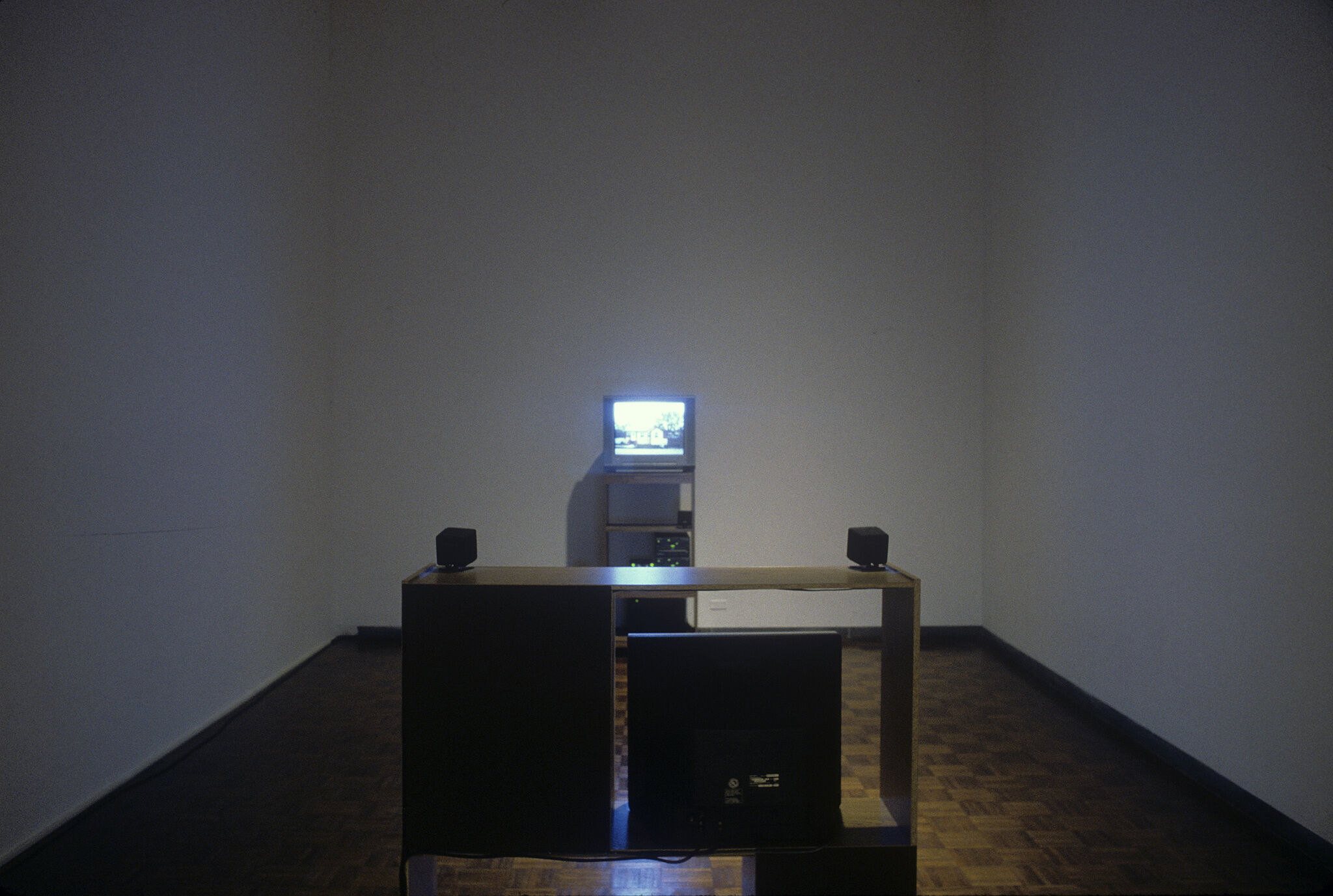 A gallery with an installation made up of a small television set with a shelf displayed in front of it.