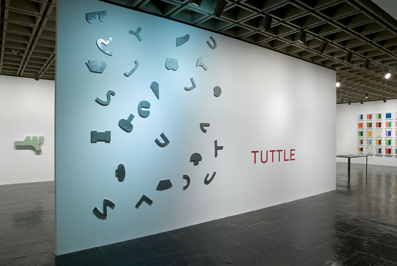 """A gallery with a white and blue gradient wall with text that reads, """"Tuttle""""."""