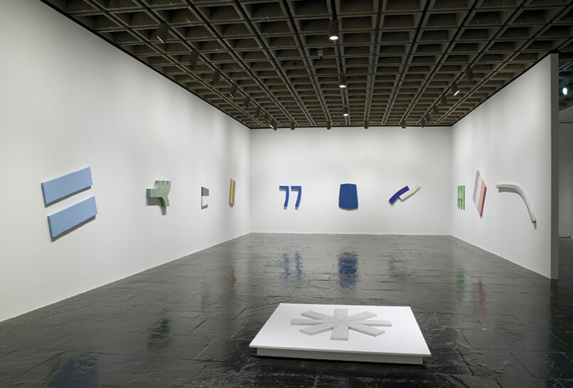 Colorful abstract sculptures displayed on the walls of a gallery.
