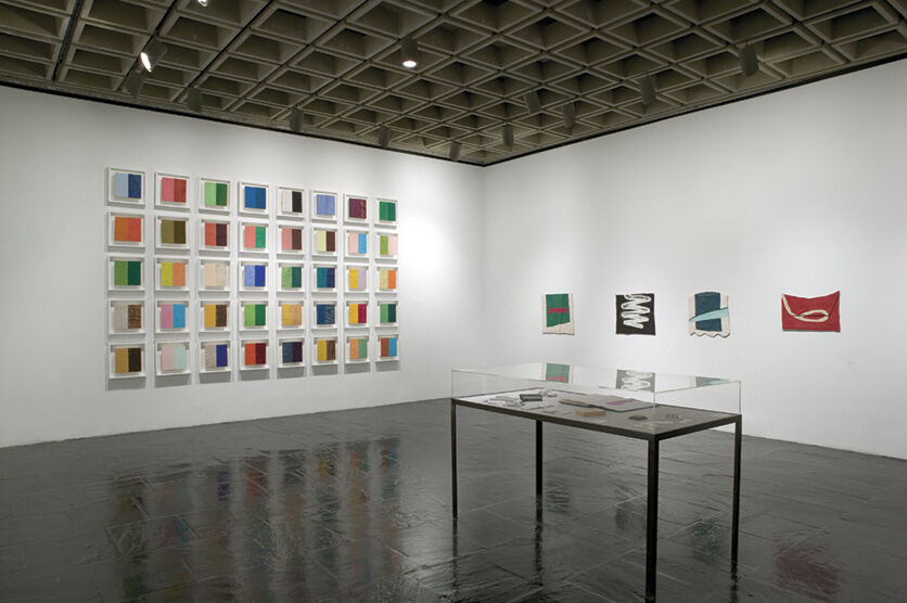 A gallery filled with various colorful abstract art displayed on the walls and in a display case.