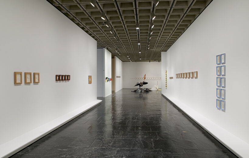 A gallery filled with various works of art including sculptures and prints displayed in small frames.