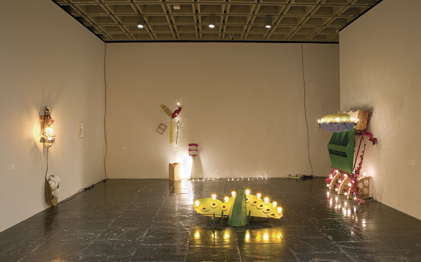 A gallery filled with sculptures with various light sources, including string lights and small lightbulbs.