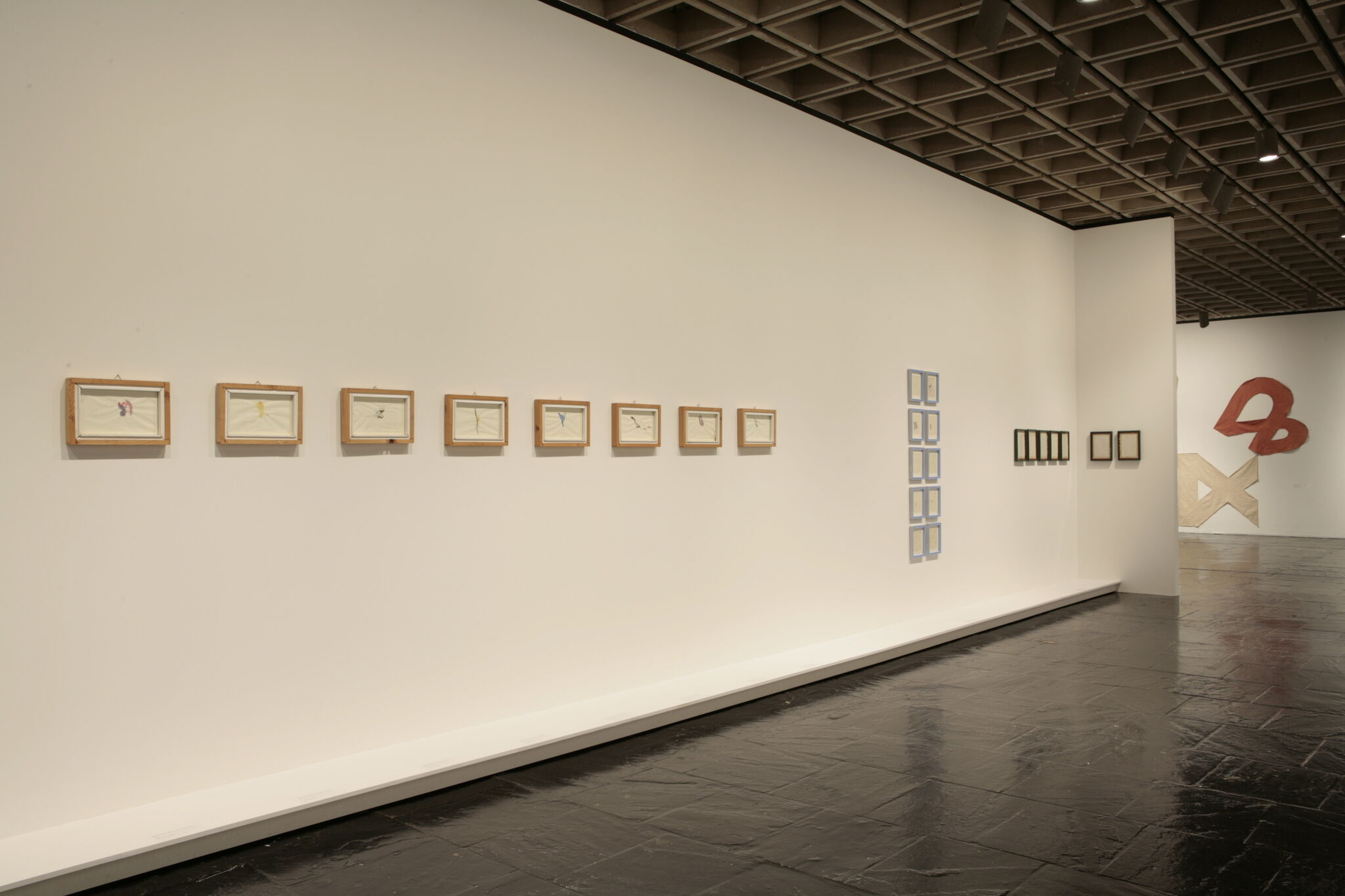 A wall in a gallery filled with small frames displaying prints.