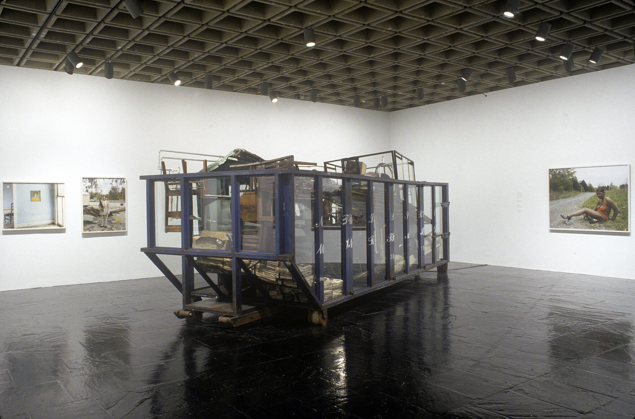 A gallery filled with photographs and a large sculpture of a glass dumpster filled with various objects.
