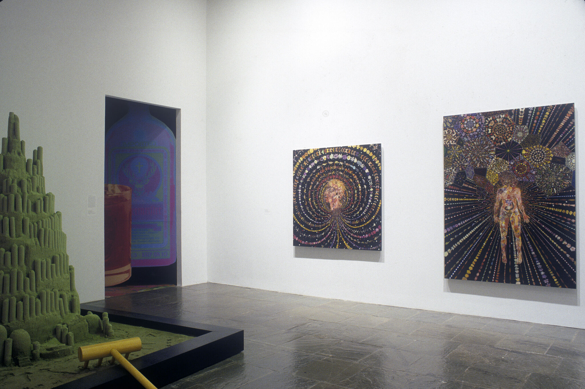 Three abstract paintings displayed in a gallery along with a green sculpture.
