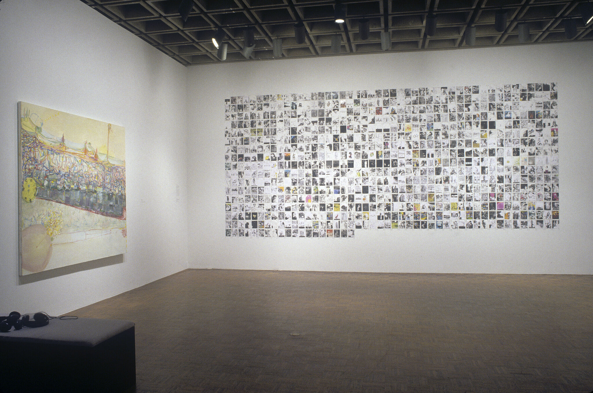 A gallery wall filled with tiny drawings that create a grid, along with a large painting displayed on another wall.