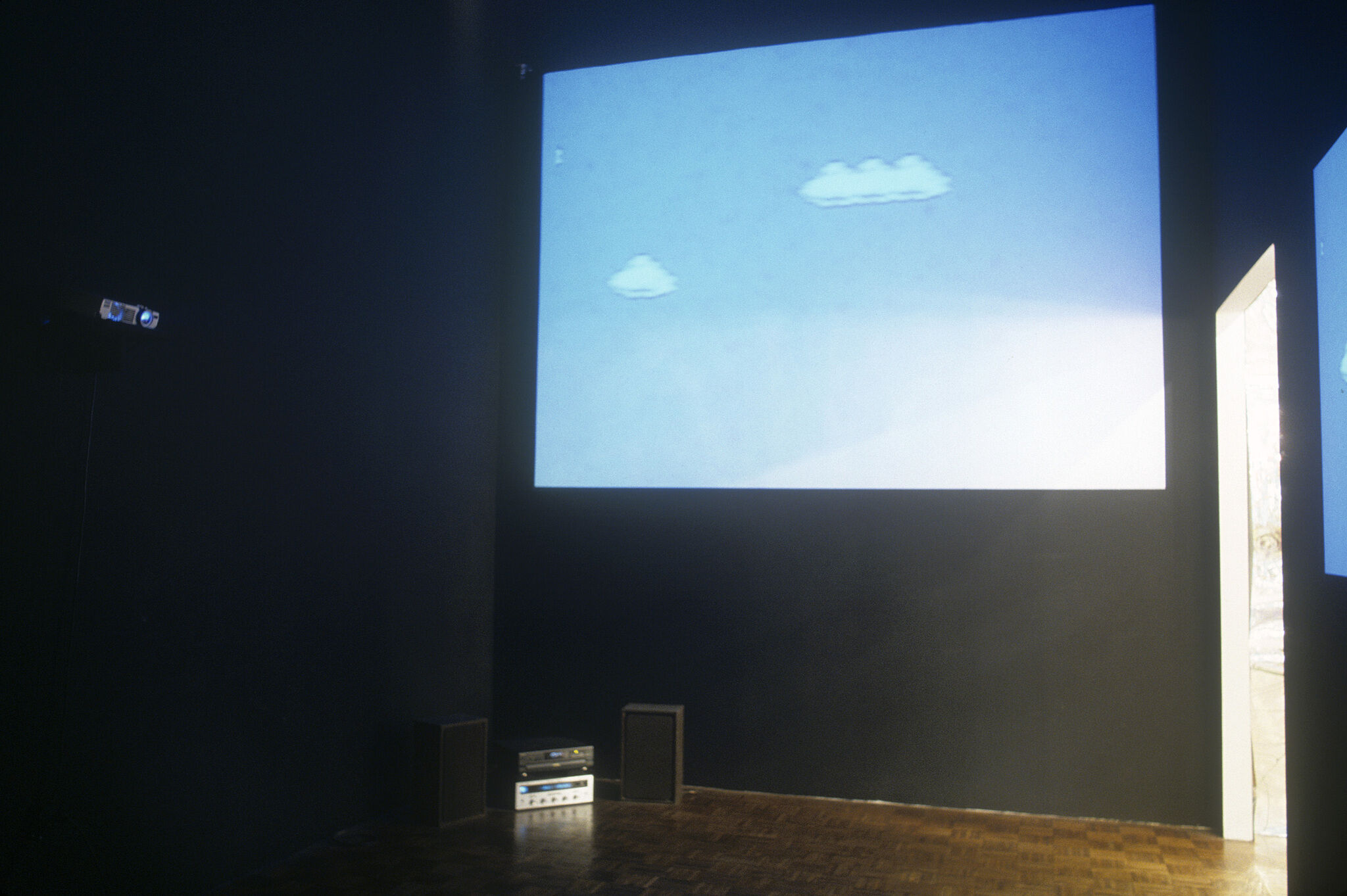 A gallery with dark walls displaying a projection of a blue sky with pixelated clouds.