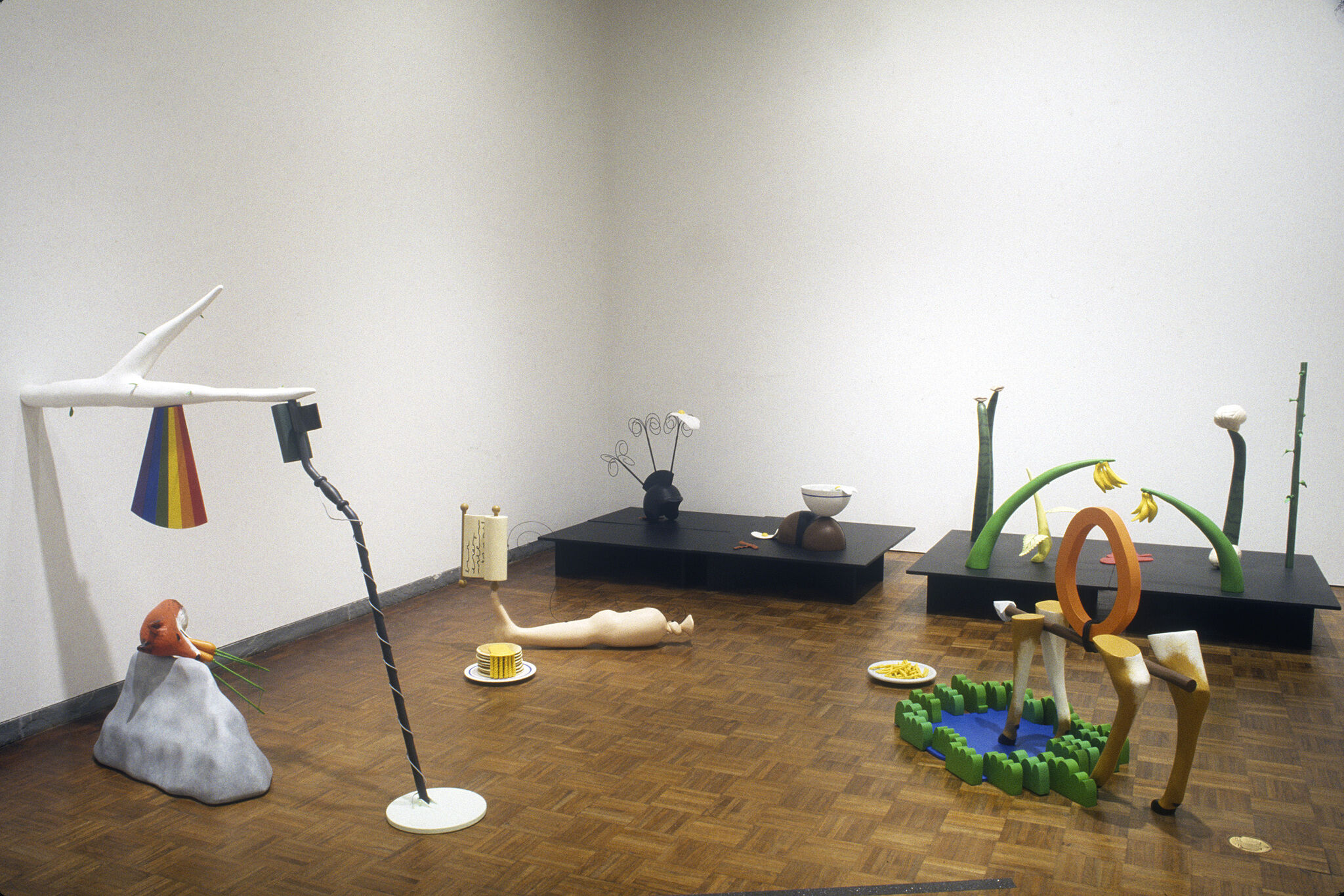 Various sculptures displayed on the floor of a gallery.