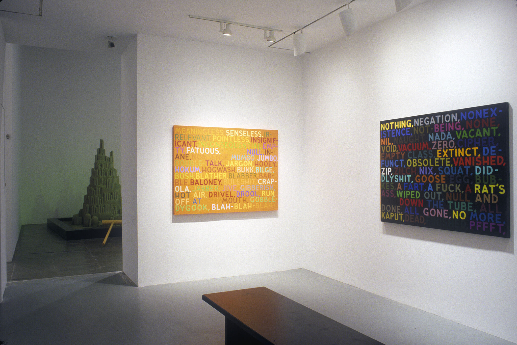 An orange painting covered in text, along with a black paintings covered in text.