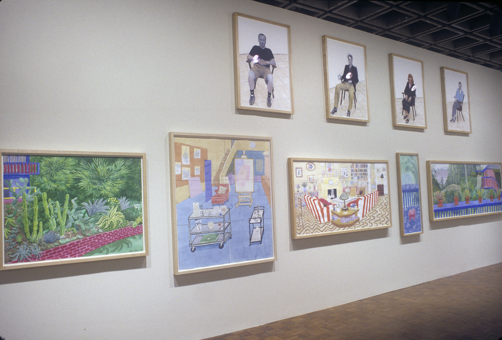 A wall in a gallery filled with art work by David Hockney.