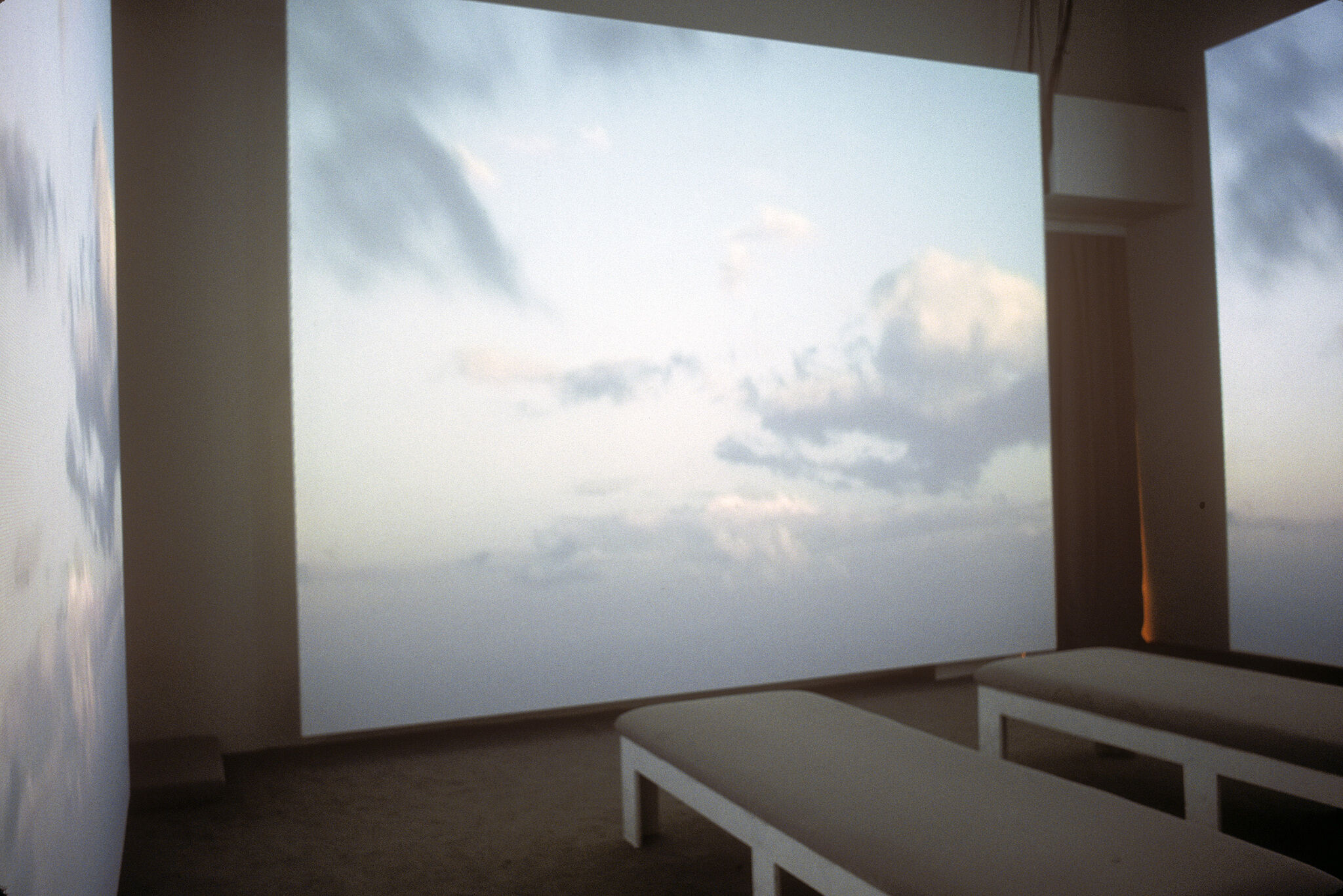 A gallery with walls covered in a projection of a sky with clouds.