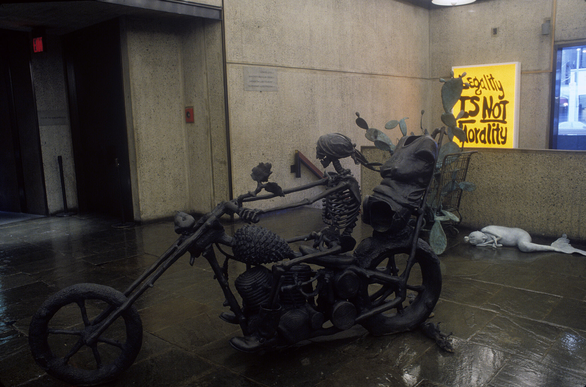 A sculpture of a skeleton on a bike.