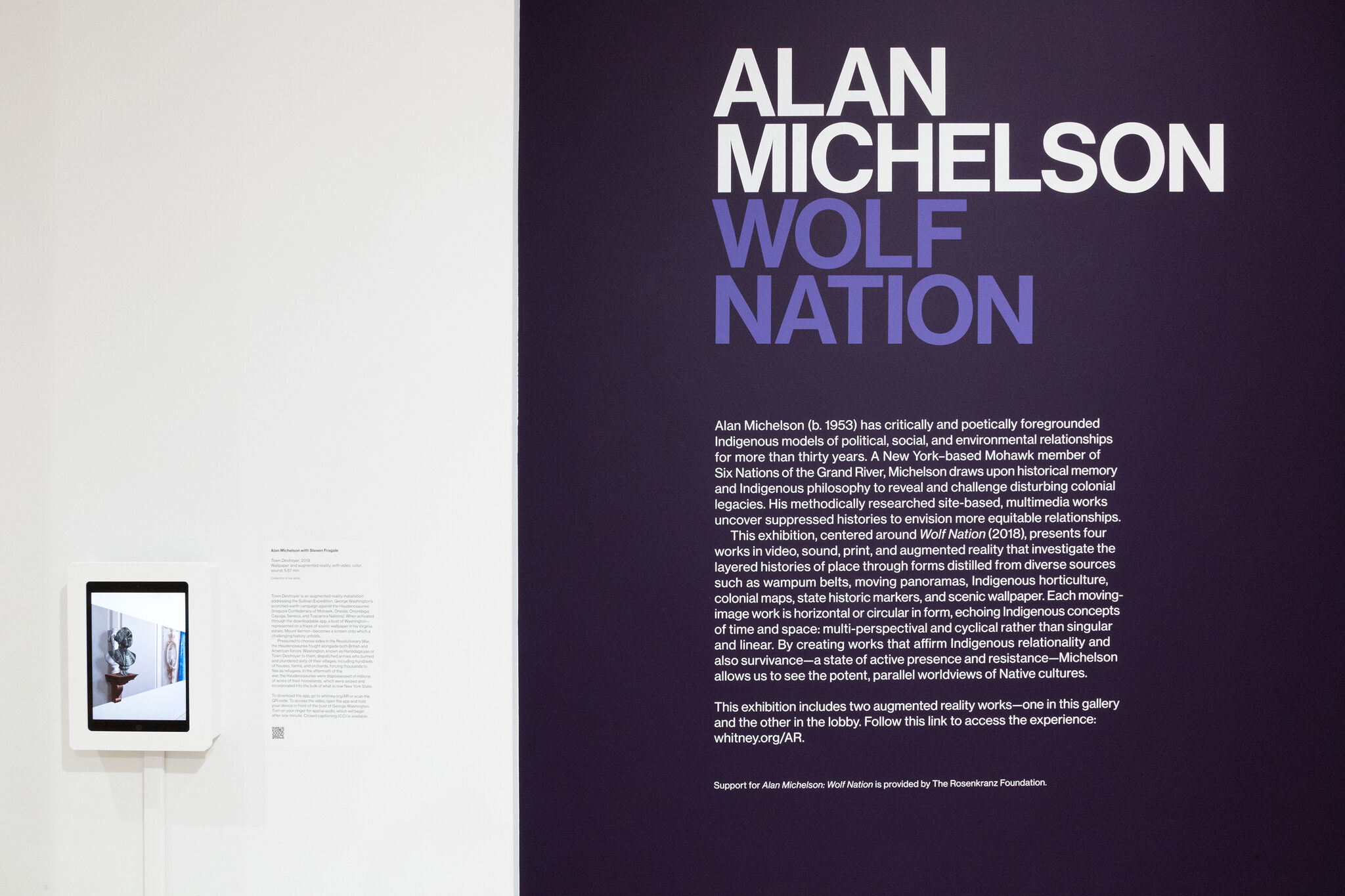 Wall text for the exhibition, Alan Michelson: Wolf Nation, along with a tablet on display.