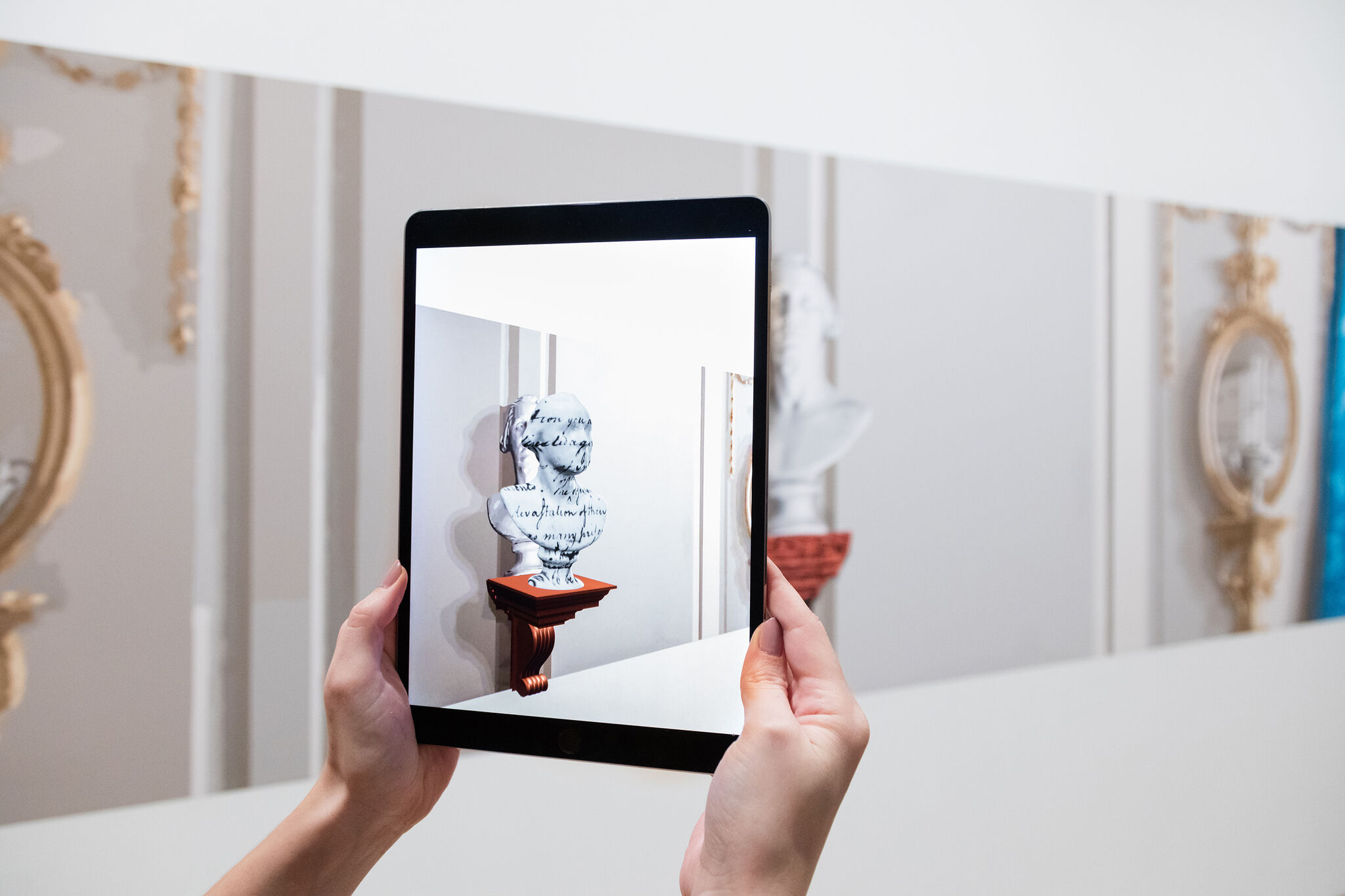 Hands holding a tablet with an augmented reality app showing a 3D view of the artwork in front of it.