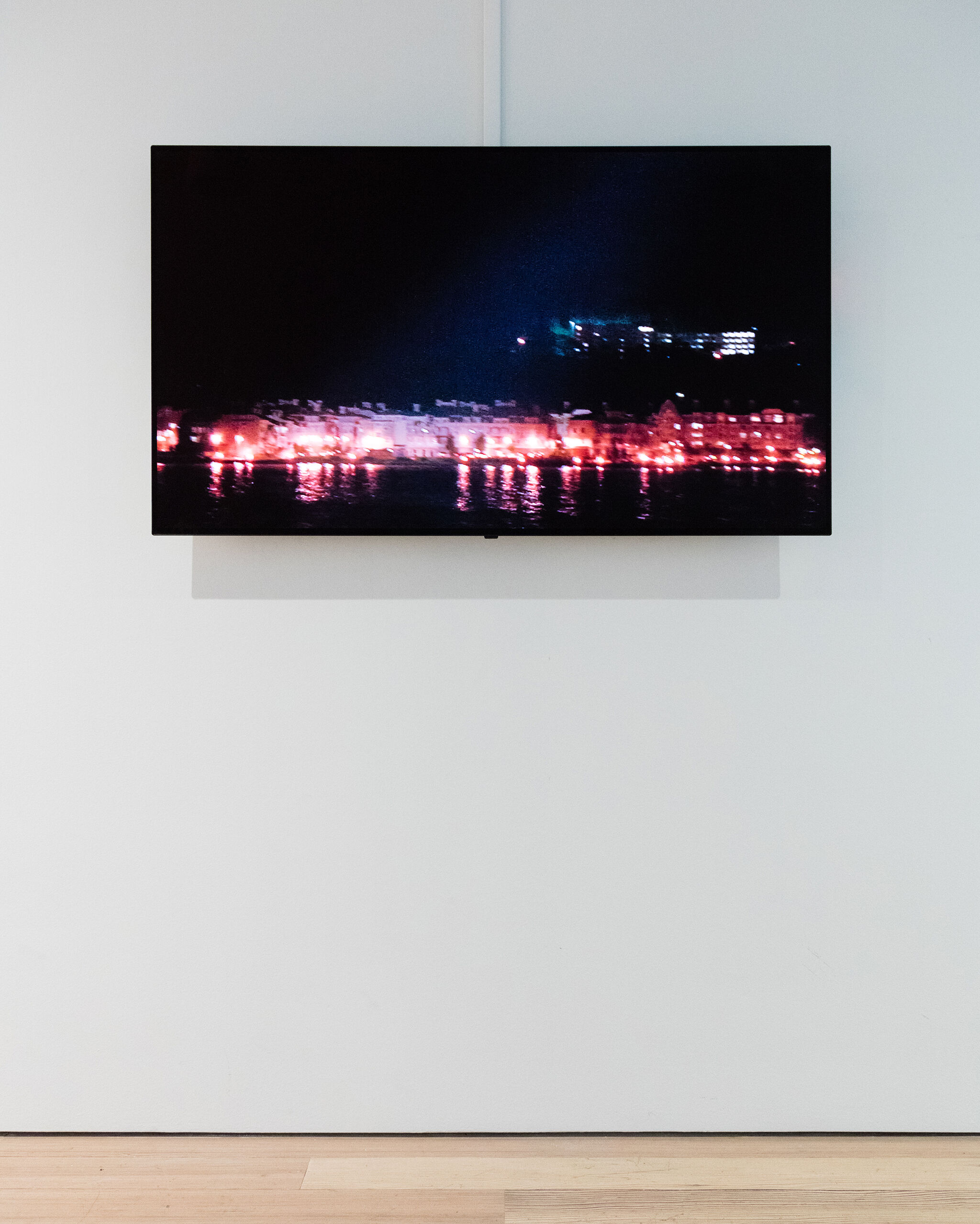 A monitor in a gallery displaying a nighttime red hued waterfront view.