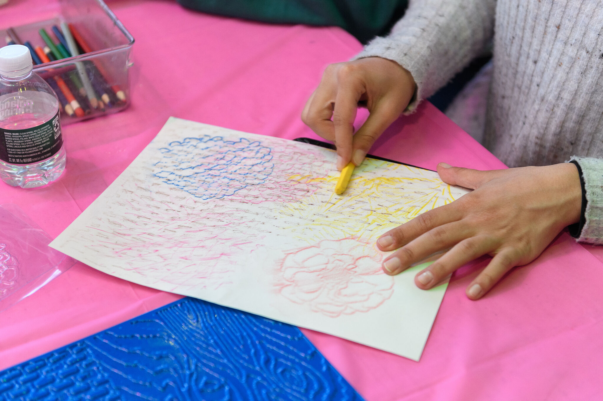 A person's hands lay over a piece of construction paper as they use a crayon to shade over a drawing.