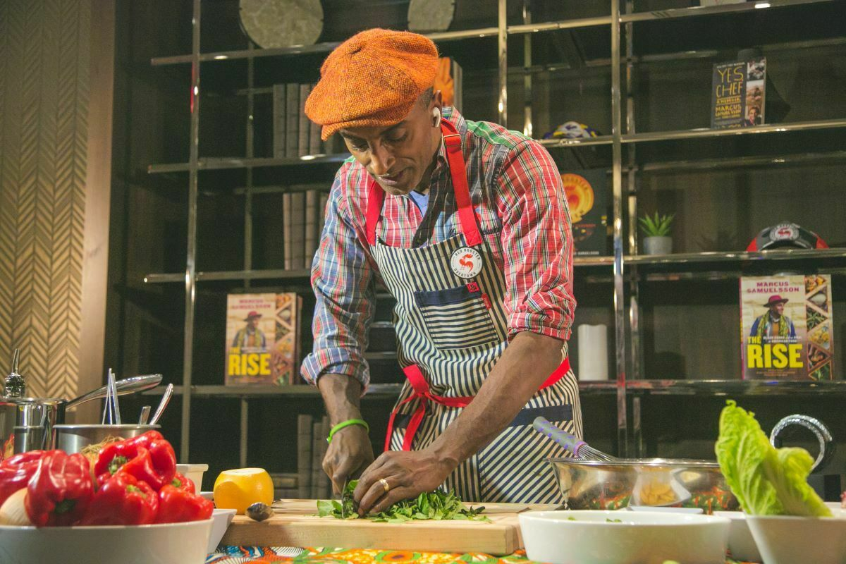Marcus Samuelsson stands over a cutting board, chopping greens with a chef's knife.