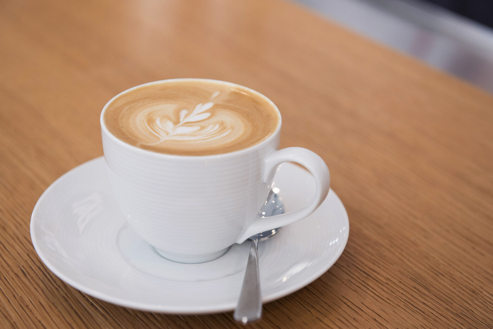 A cup of coffee in a white mug and saucer on a wooden table