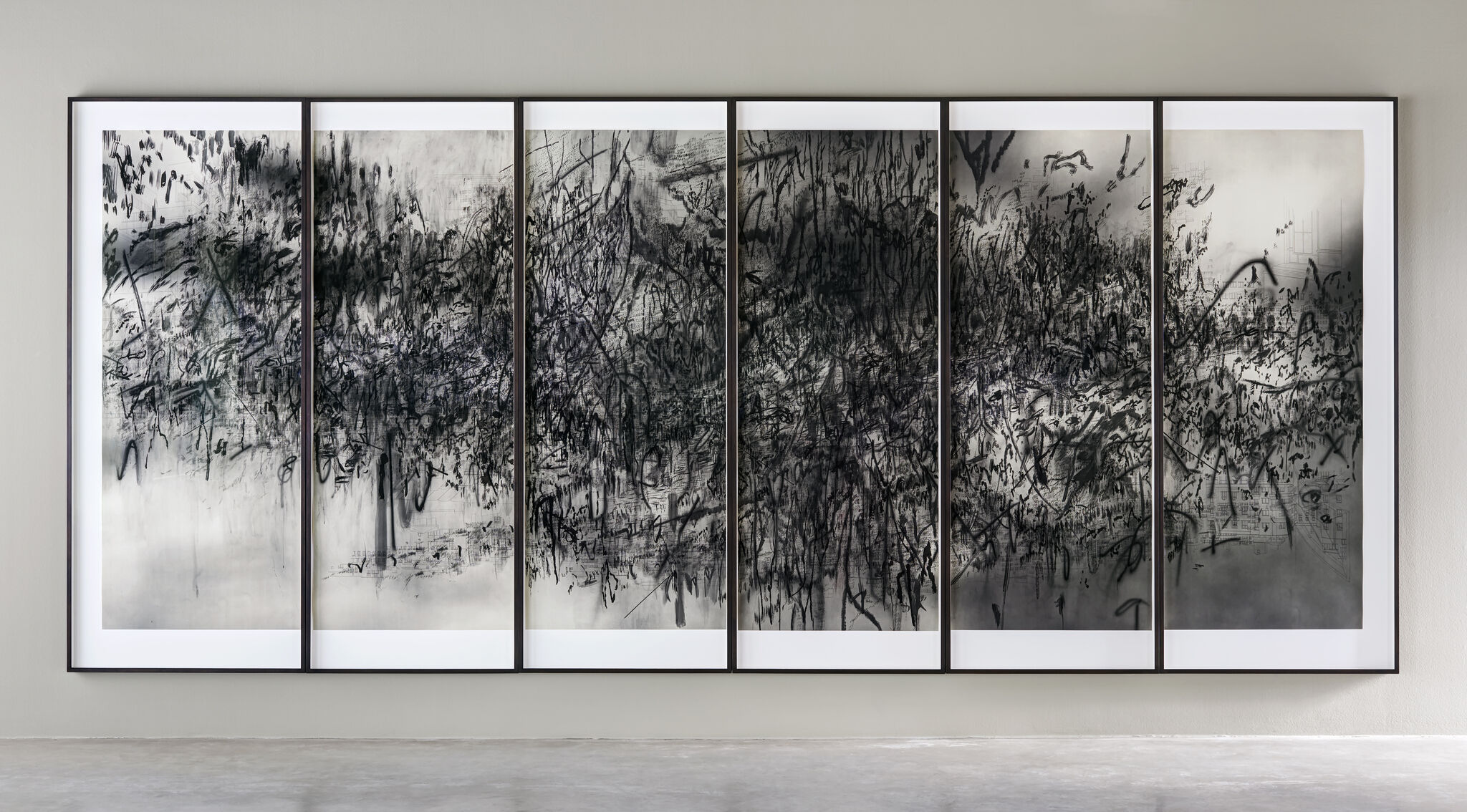 A flurry of dark strokes span the length of a wall-mounted print that's separated across six framed panels.