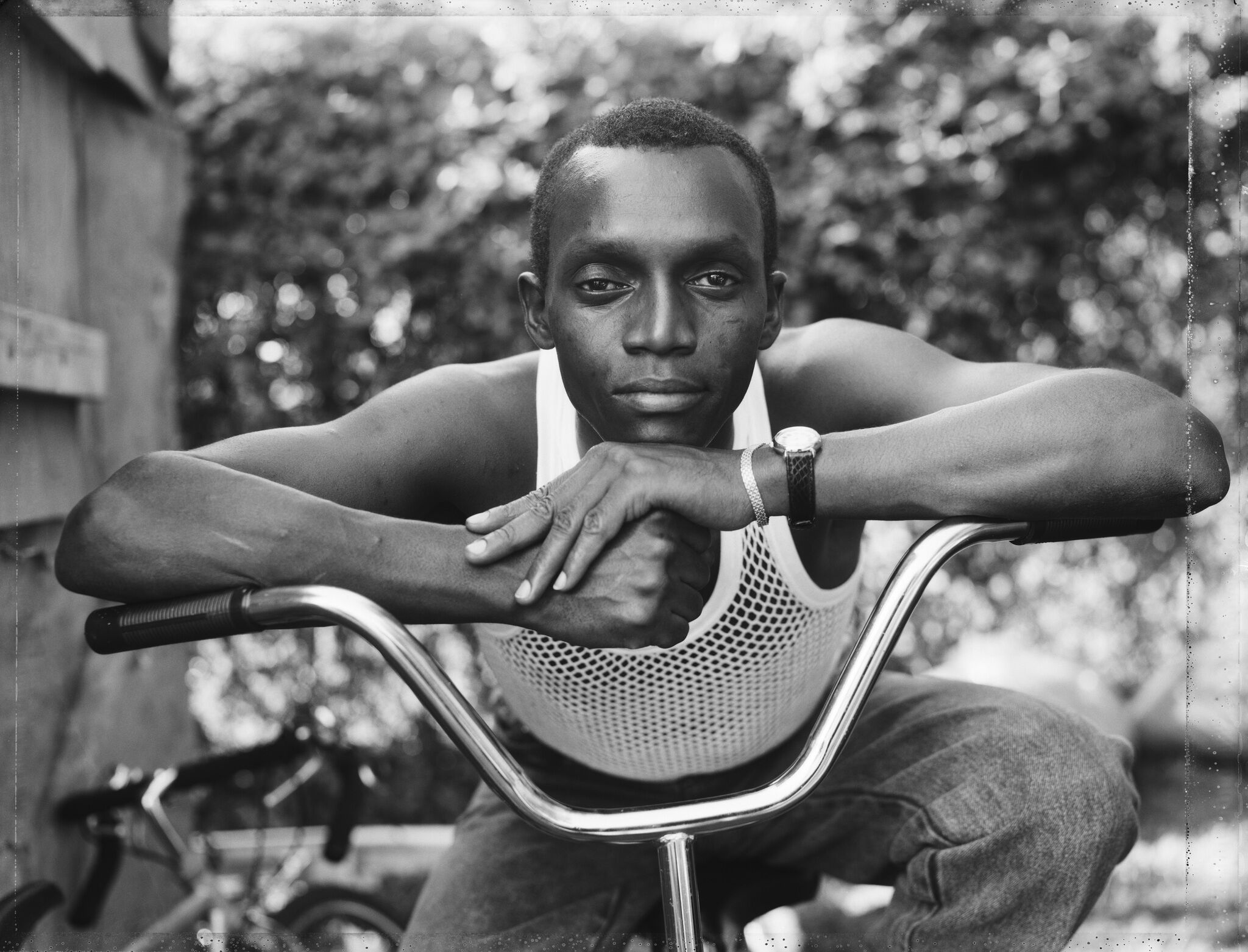 A young man is sitting on a bike and resting his arms on the handles.
