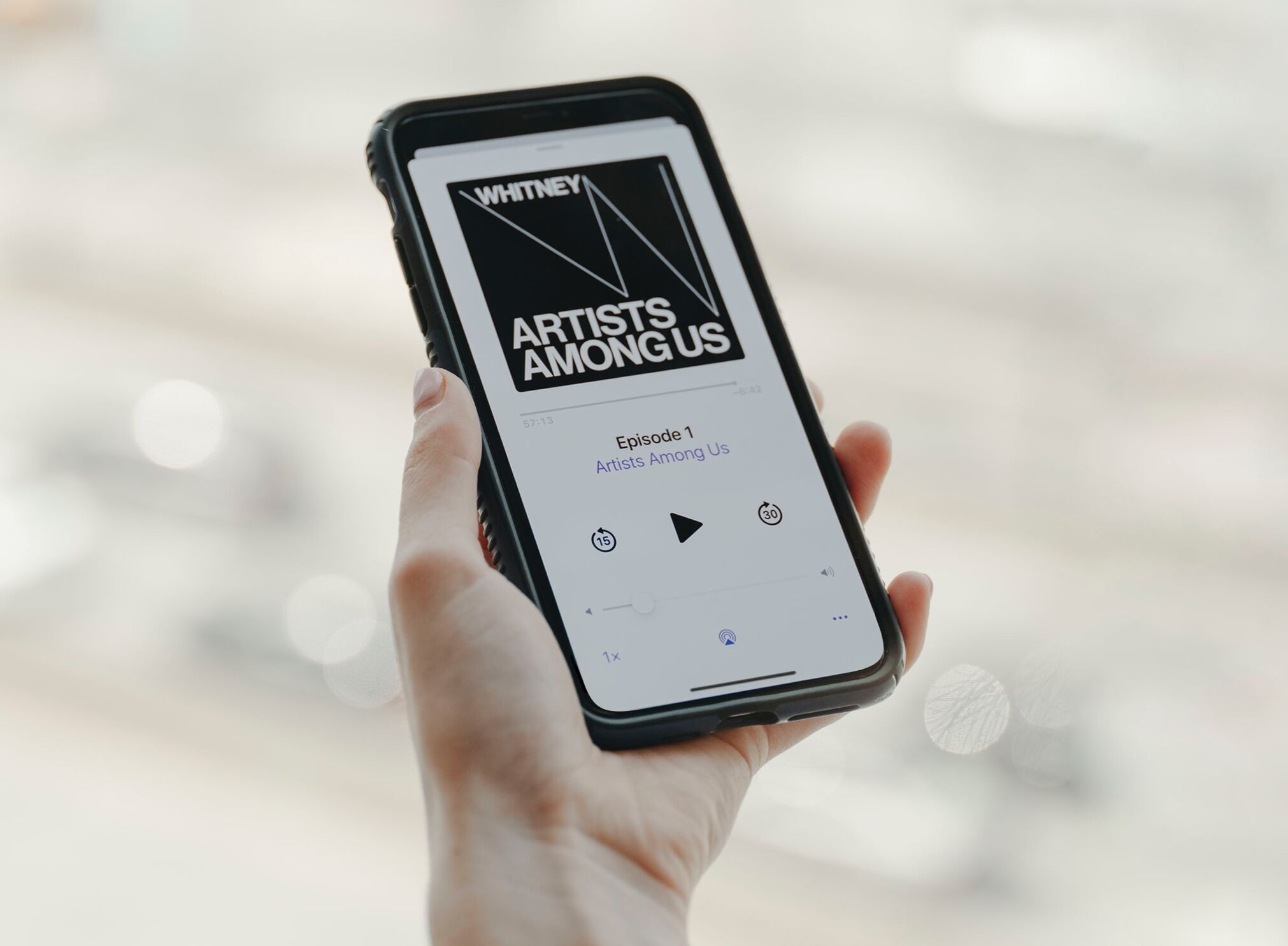 A hand holding a smartphone whose screen displays the Artists Among Us podcast playing.