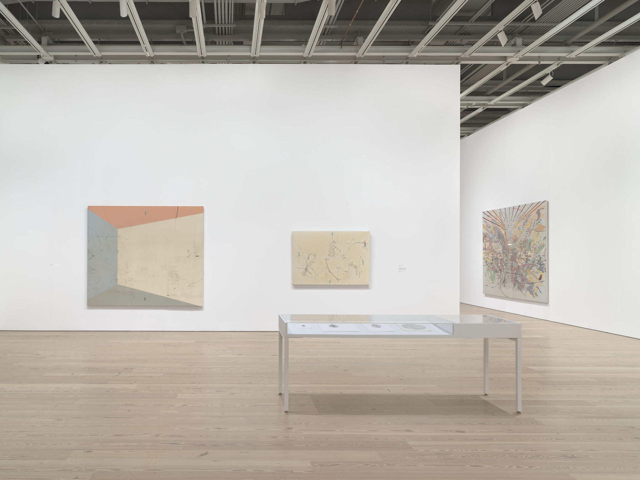 A main exhibition room of the Whitney with three pieces mounted on two separate walls.