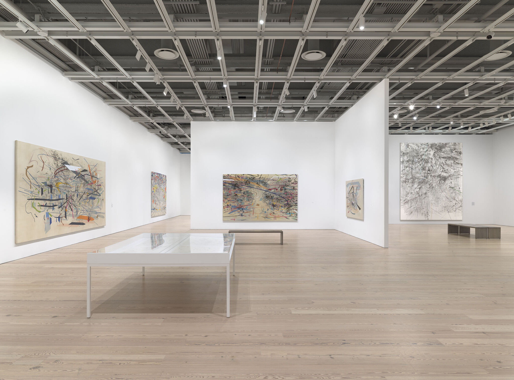 A main exhibition room of the Whitney with five pieces mounted on the walls across the space.