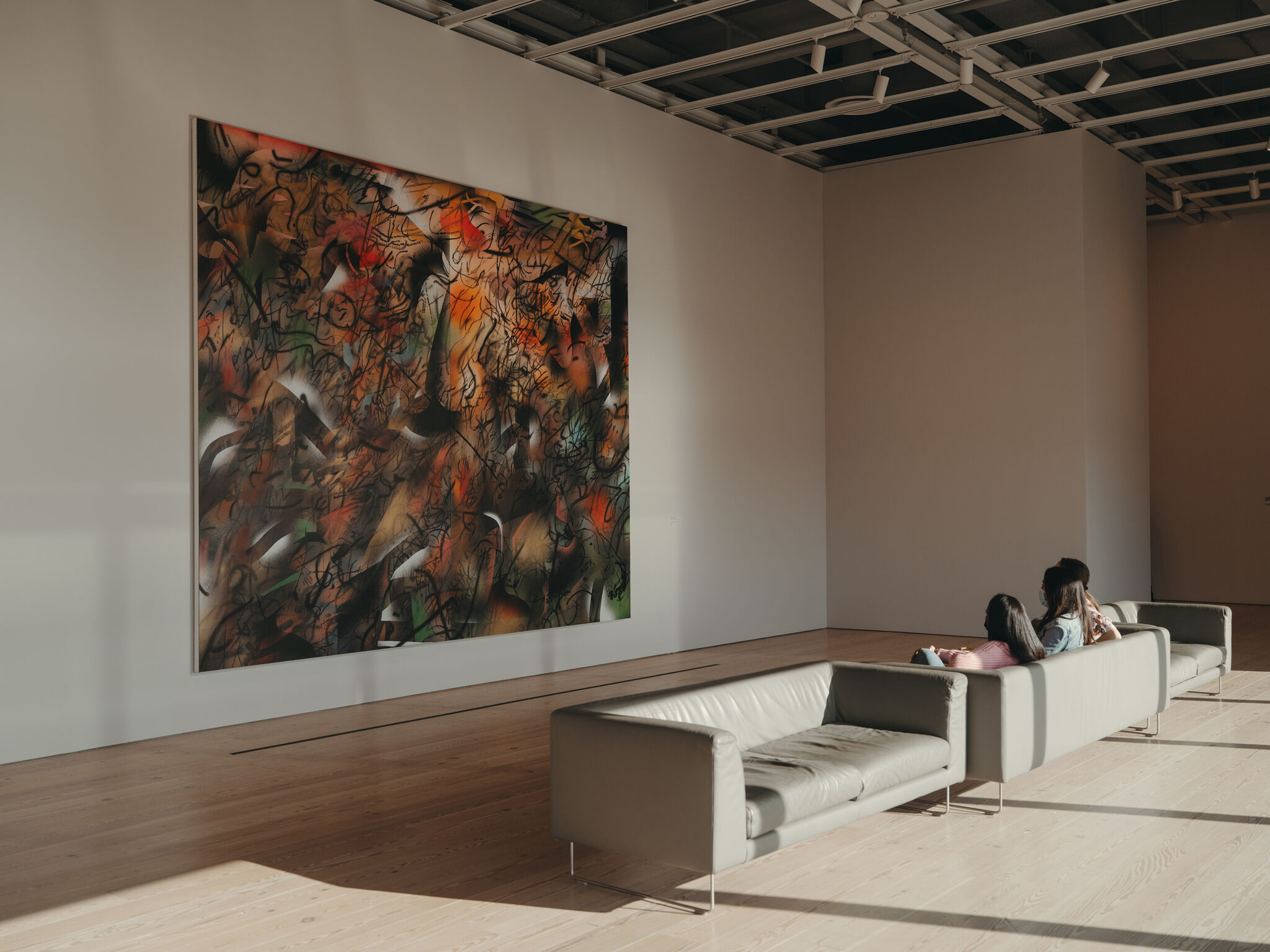 A colorful, abstract, large-scale painting by Julie Mehretu with visitors viewing it seated from a couch.