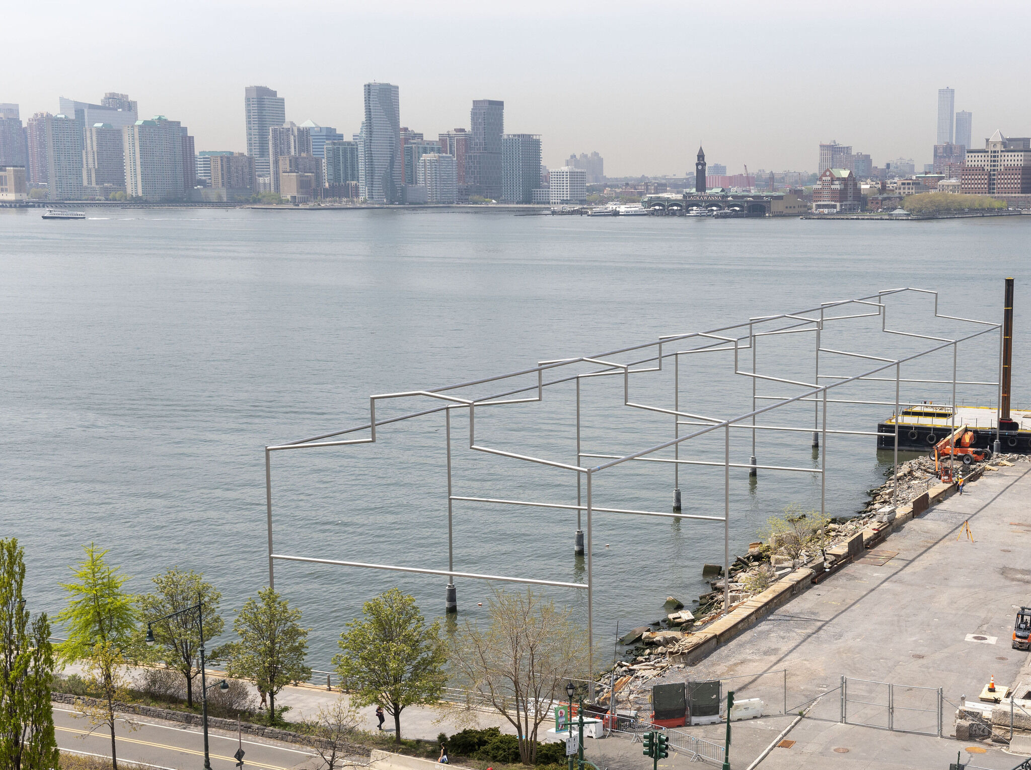 Birds-eye view of large steel sculpture in the shape of a building outline, extending from the Manhattan shoreline into the Hudson River, with a view of the New Jersey skyline in the background.