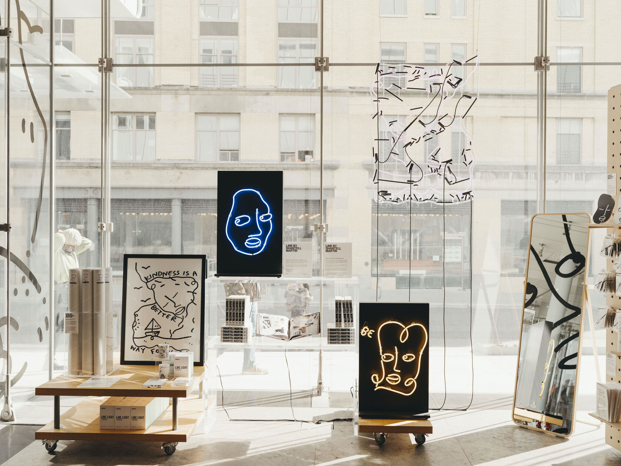 A series of merchandise staged in front of a glass window in the Whitney shop.