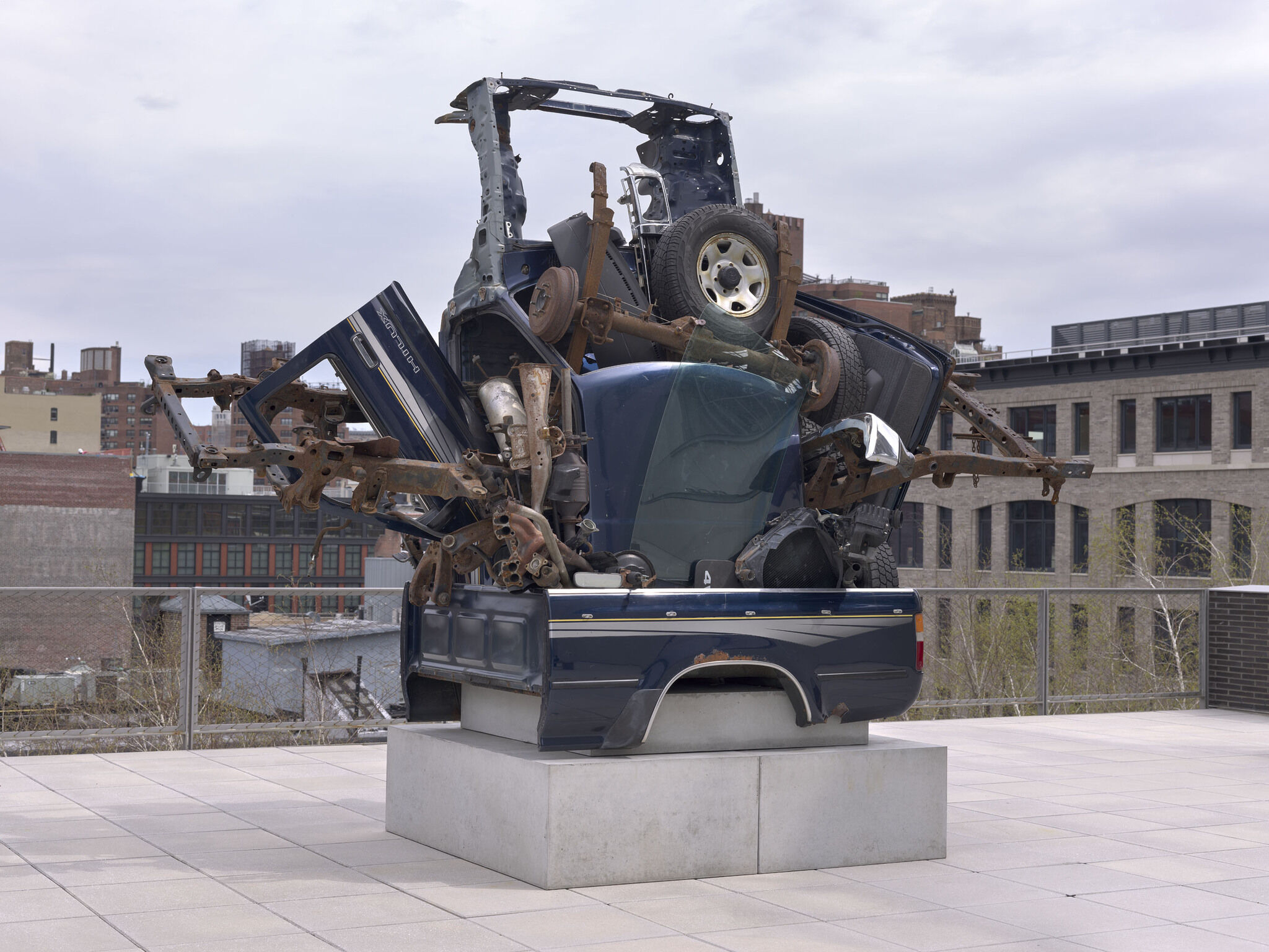 A sculpture constructed from automotive parts positioned on the balcony outside the Whitney.
